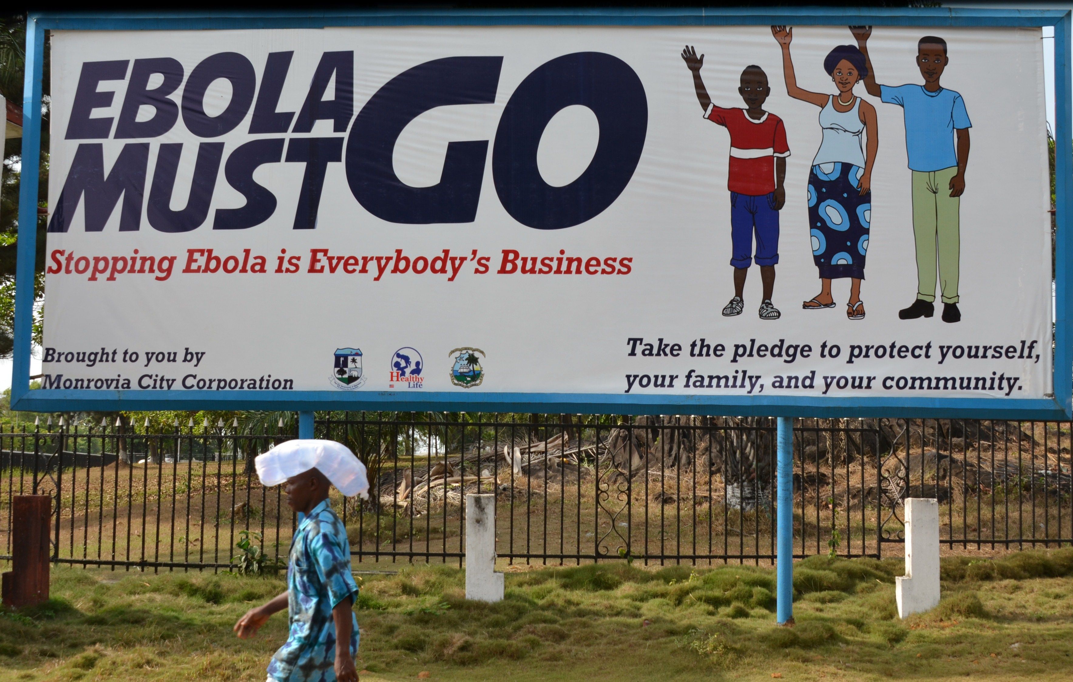 A man walks past an ebola campaign banner with the new slogan  Ebola Must GO  in Monrovia, Liberia on Feb. 23, 2015.