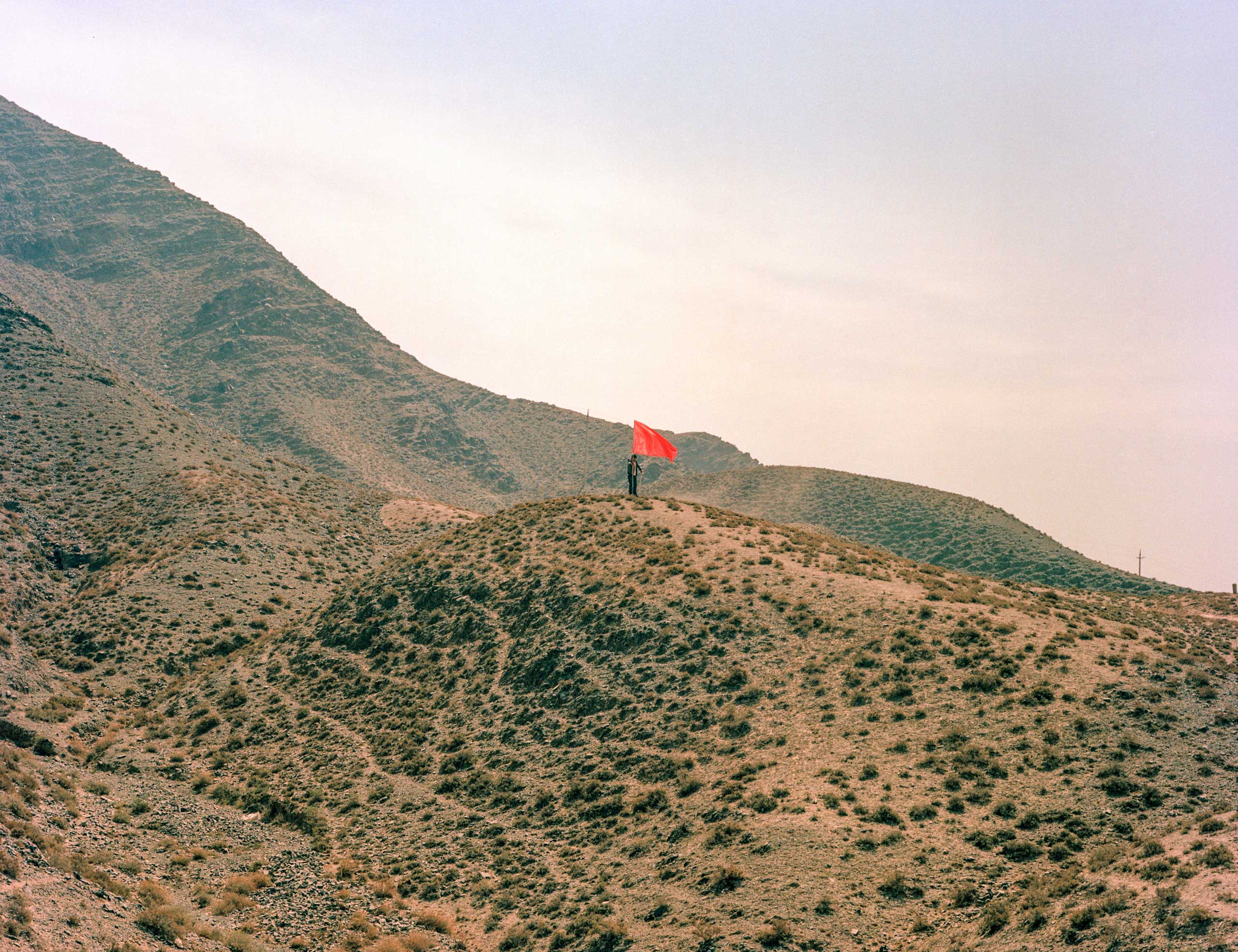 A road builder raises a red flag on a hillside in Jinchuan Valley, Gansu Province, China.