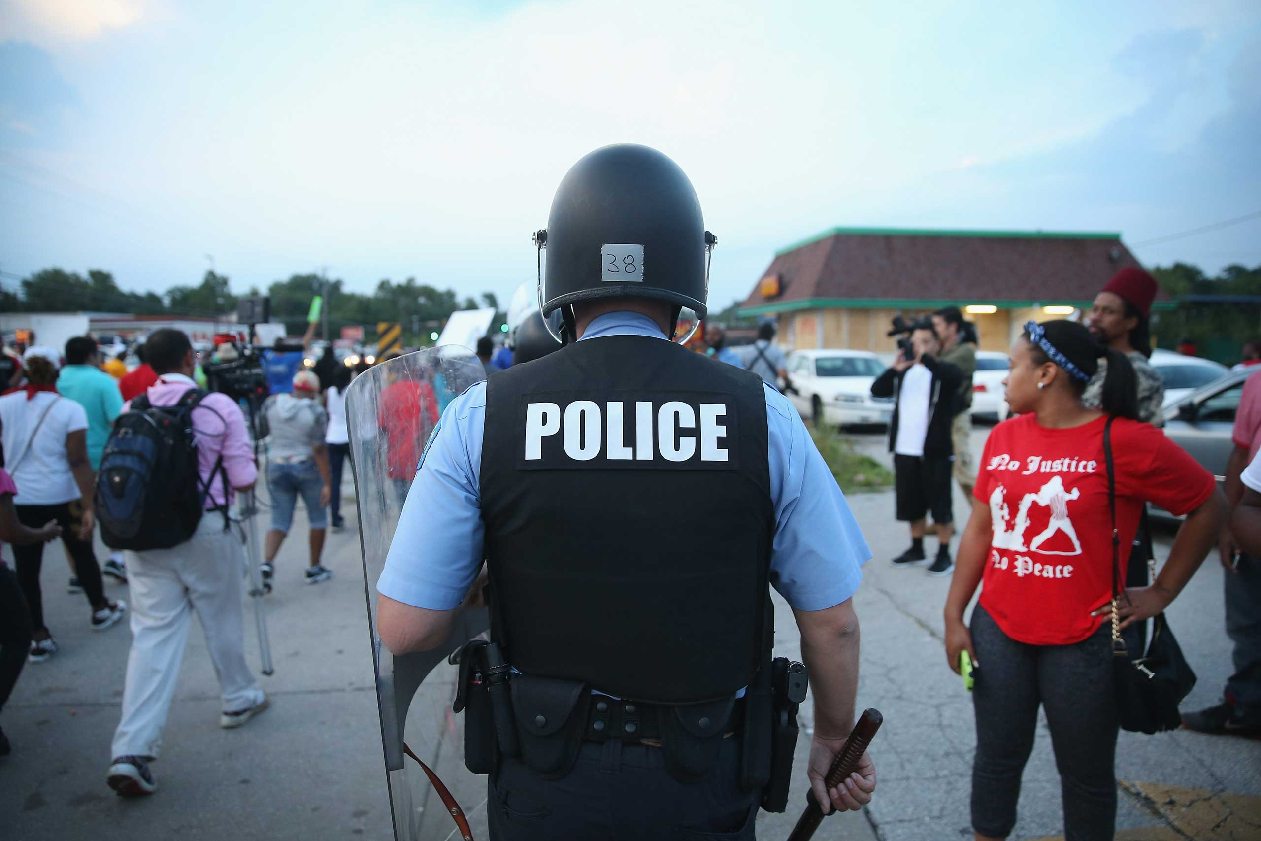 Police are deployed to keep peace along Florissant Avenue in Ferguson, Mo. on Aug. 16, 2014.