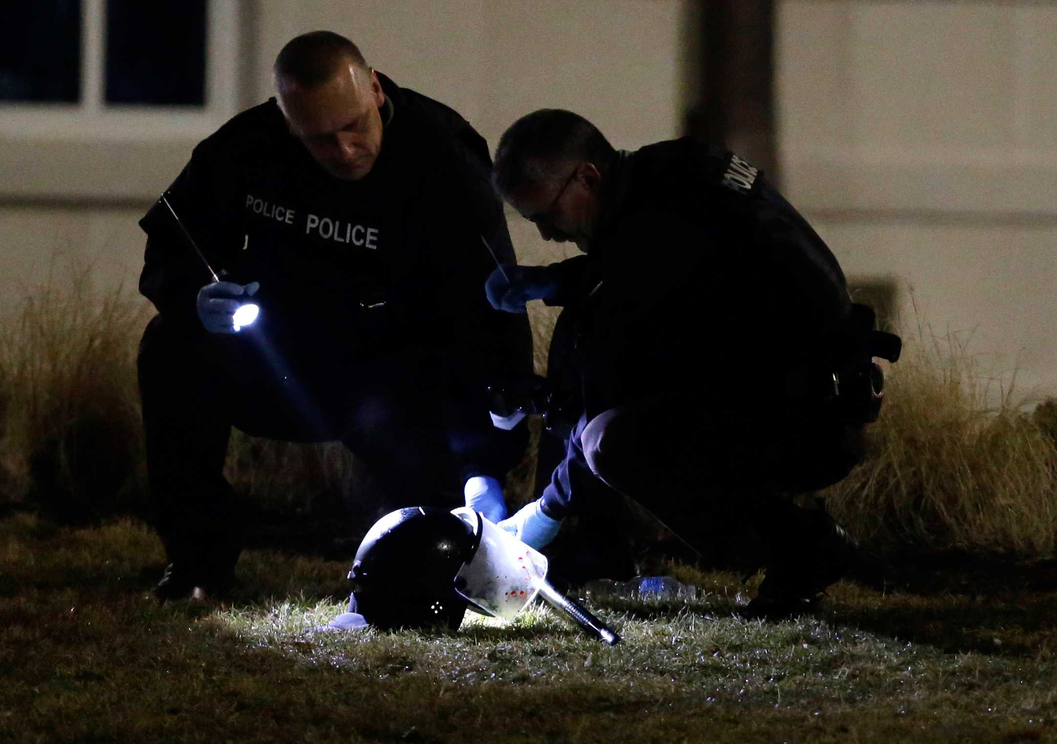 Police shine a light on a helmet as they investigate the scene where two police officers were shot outside the Ferguson Police Department Thursday, March 12, 2015, in Ferguson, Mo.