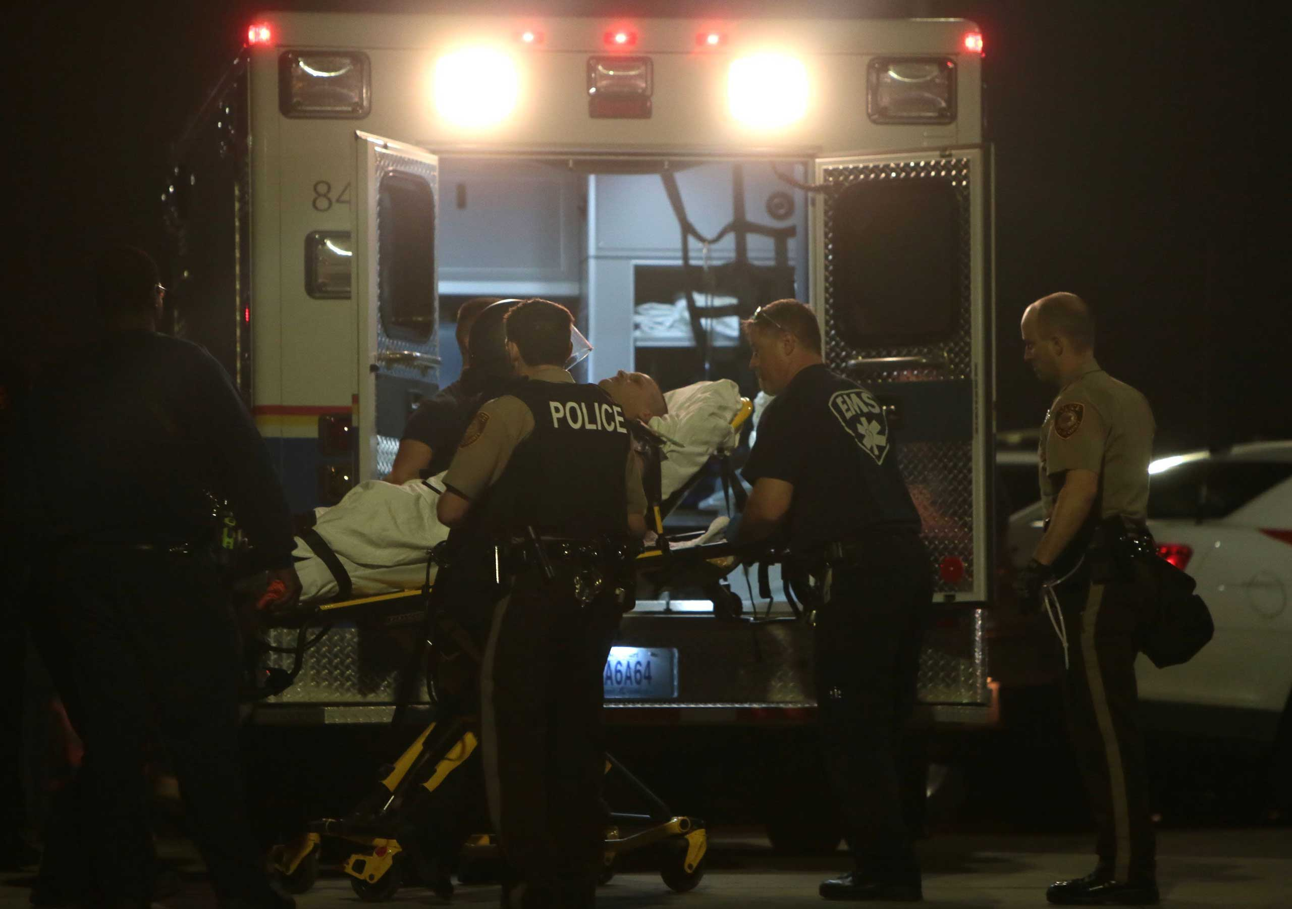 Paramedics load one of two police officer who were shot while standing guard in front of the Ferguson Police Station during a protest on March 12, 2015.