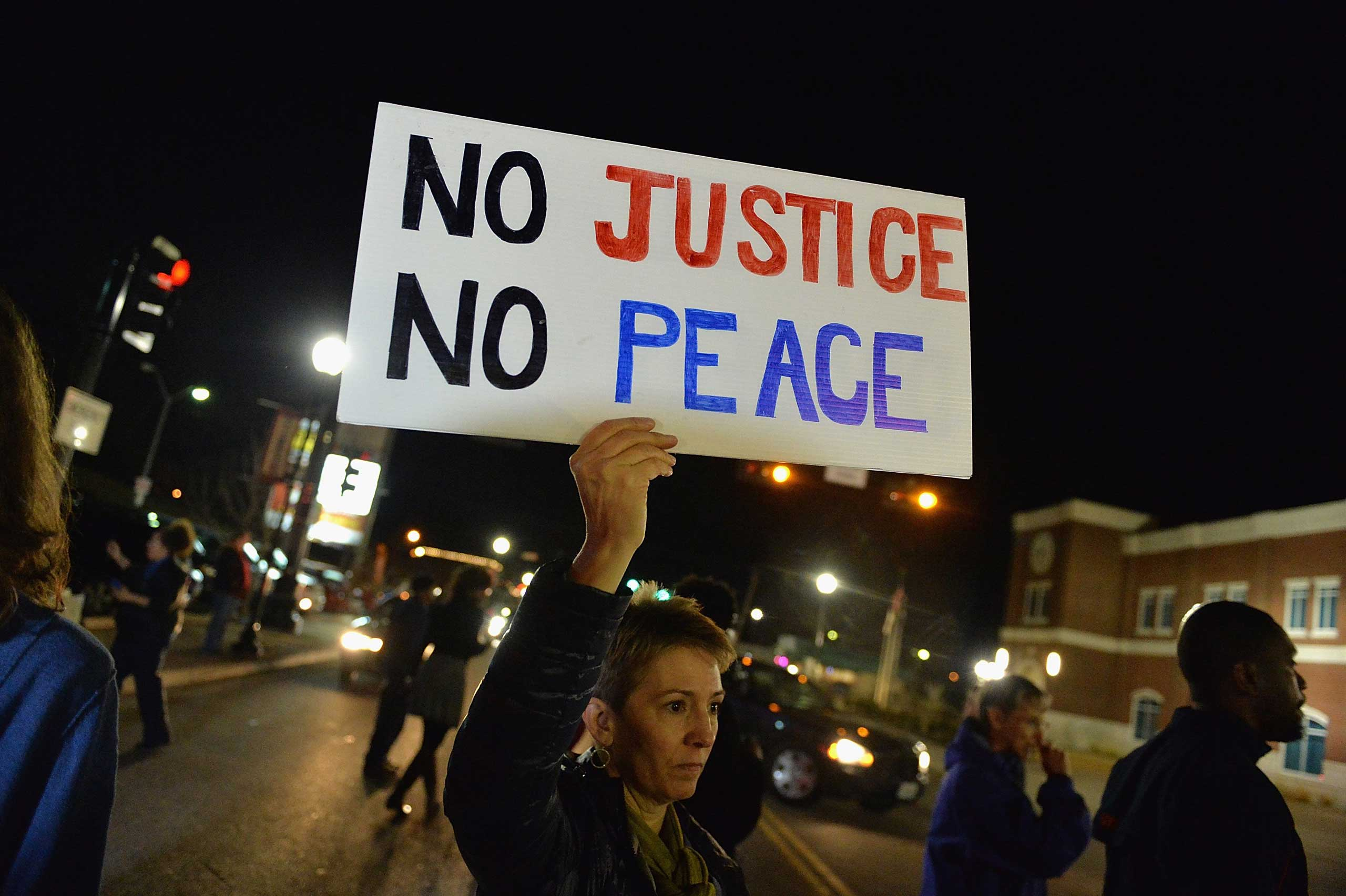 Protestors hold signs during a protest outside the Ferguson Police Department on March 11, 2015 in Ferguson.