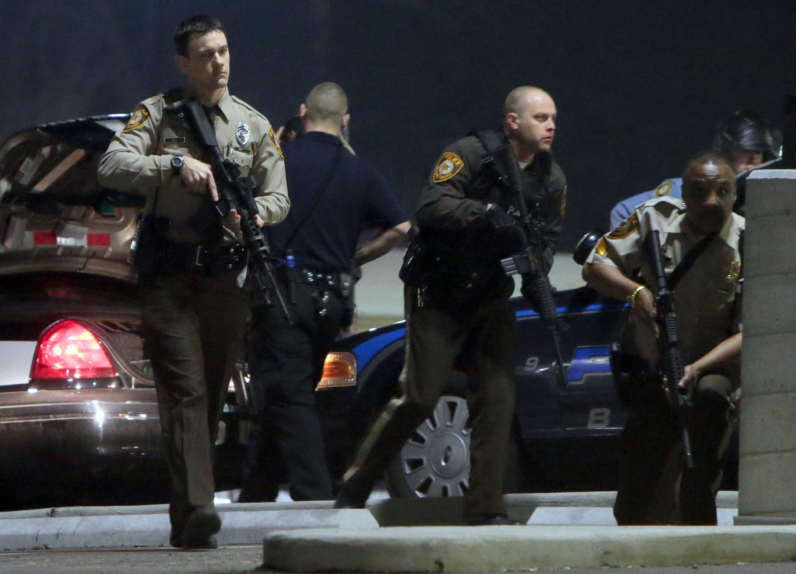 Police mobilize in the parking lot of the Ferguson Police Station after two police officers were shot while standing guard in front of the Ferguson Police Station, March 12, 2015.