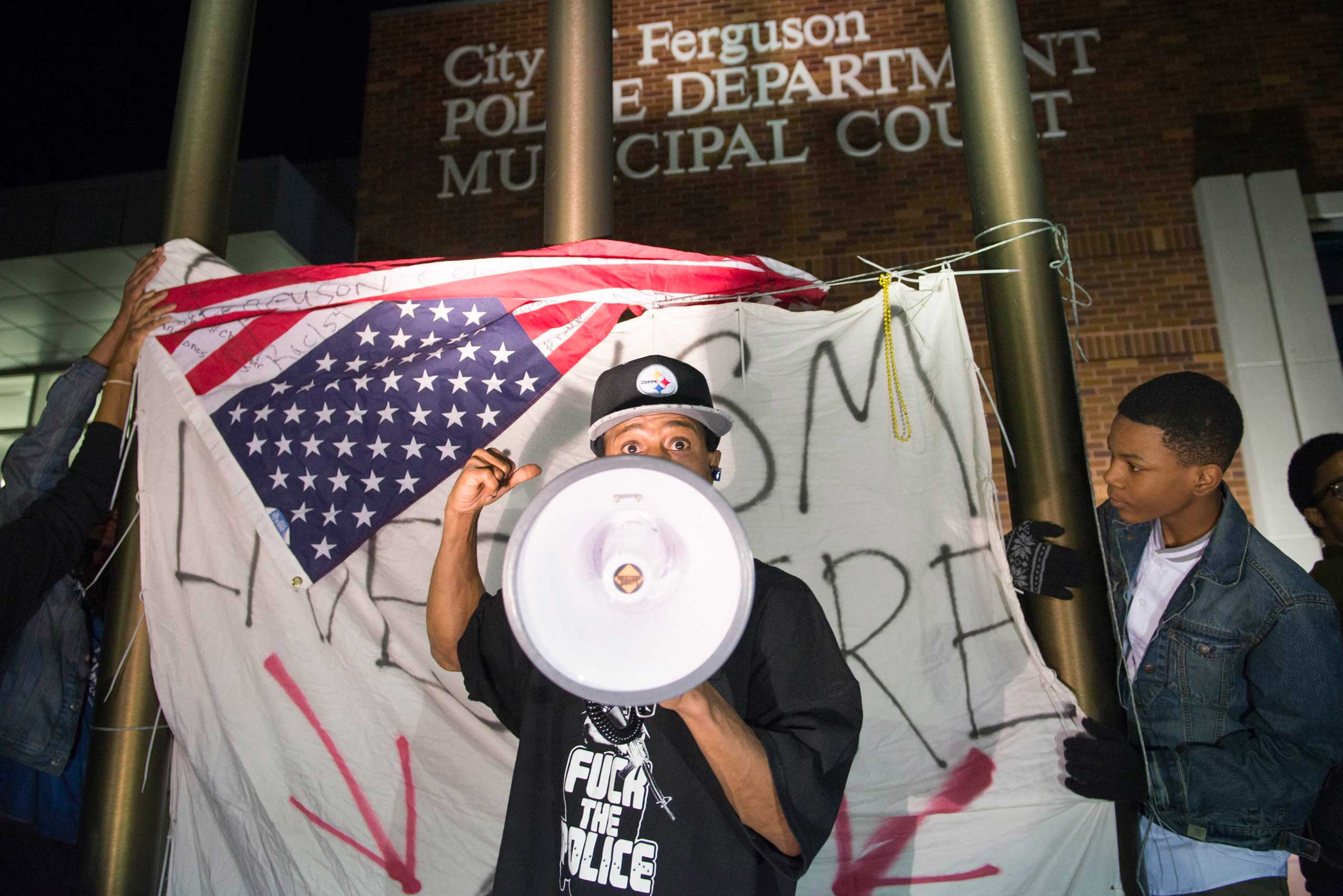 """A protester chants in front of a flag which reads, """"Racism lives here"""", outside the City of Ferguson Police Department and Municipal Court in Ferguson, March 11, 2015."""