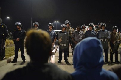 Police officers stand on alert during a protests outside the Ferguson Police Department on March 11, 2015 in Ferguson, Mo.