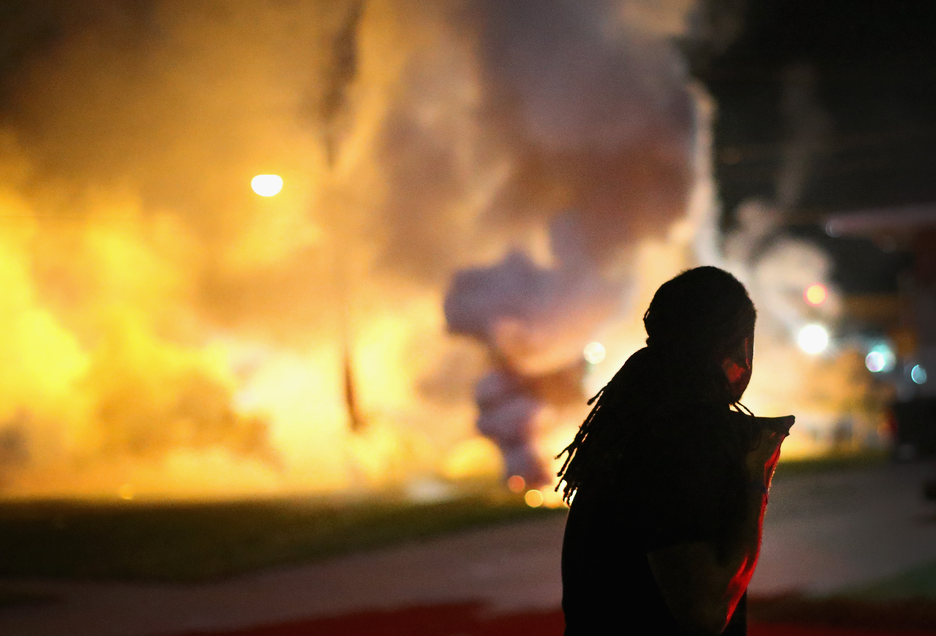 A demonstrator, protesting the shooting death of teenager Michael Brown, scrambles for cover as police fire tear gas on August 13, 2014 in Ferguson, Missouri.