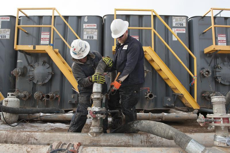 Mody Torres (L) and Josh Anderson of Select Energy Services connect hoses between a pipeline and water tanks at a Hess fracking site near Williston, North Dakota Nov. 12, 2014.