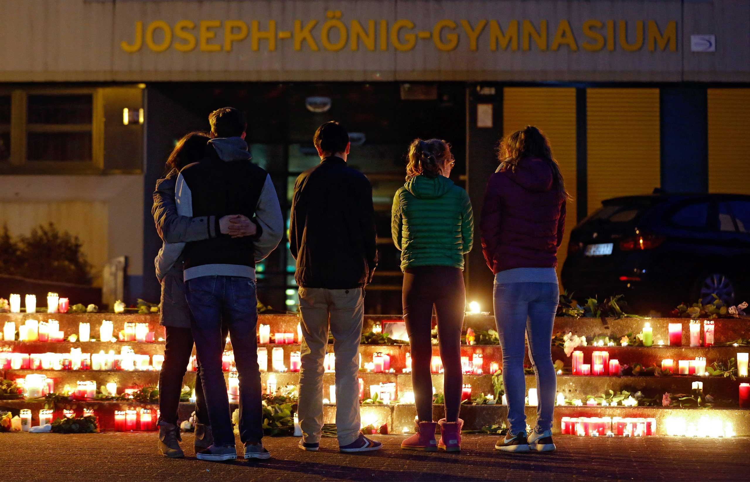 People stand in front of candles and flowers placed in front of the Joseph-Koenig-Gymnasium in Haltern, Germany, March 24, 2015.