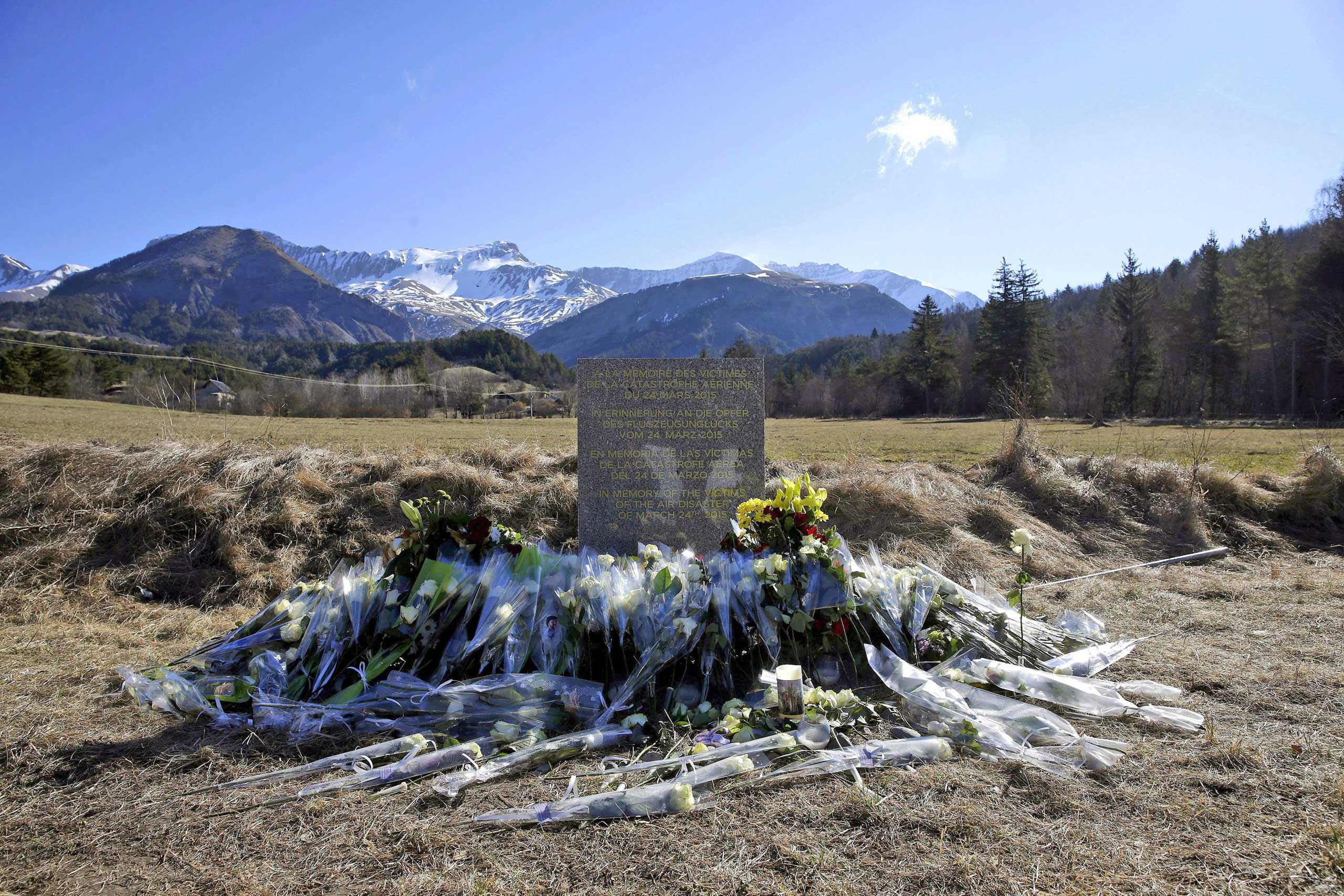 Flowers are left in front of the monument in homage to the victims of Germanwings Flight 4U 9525 in Le Vernet, southeastern France, March 27, 2015.