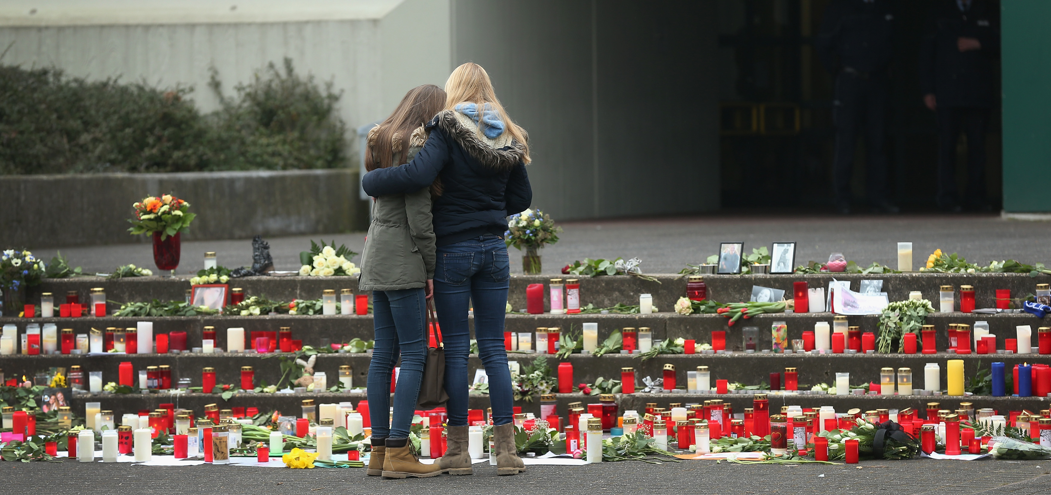 Two young women comfort one another at a high school while paying tribute to students and teachers aboard the Germanwings flight that crashed in France on March 25, 2015 in Haltern, Germany.