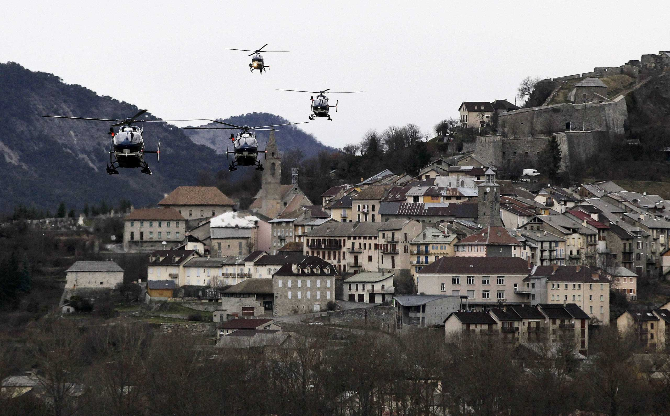 Helicopters of the French gendarmerie and emergency services fly over Seyne-les-Alpes as they resume works to recover the bodies and the remains of the Airbus A320 that crashed the previous day in the Alps, March 25, 2015.