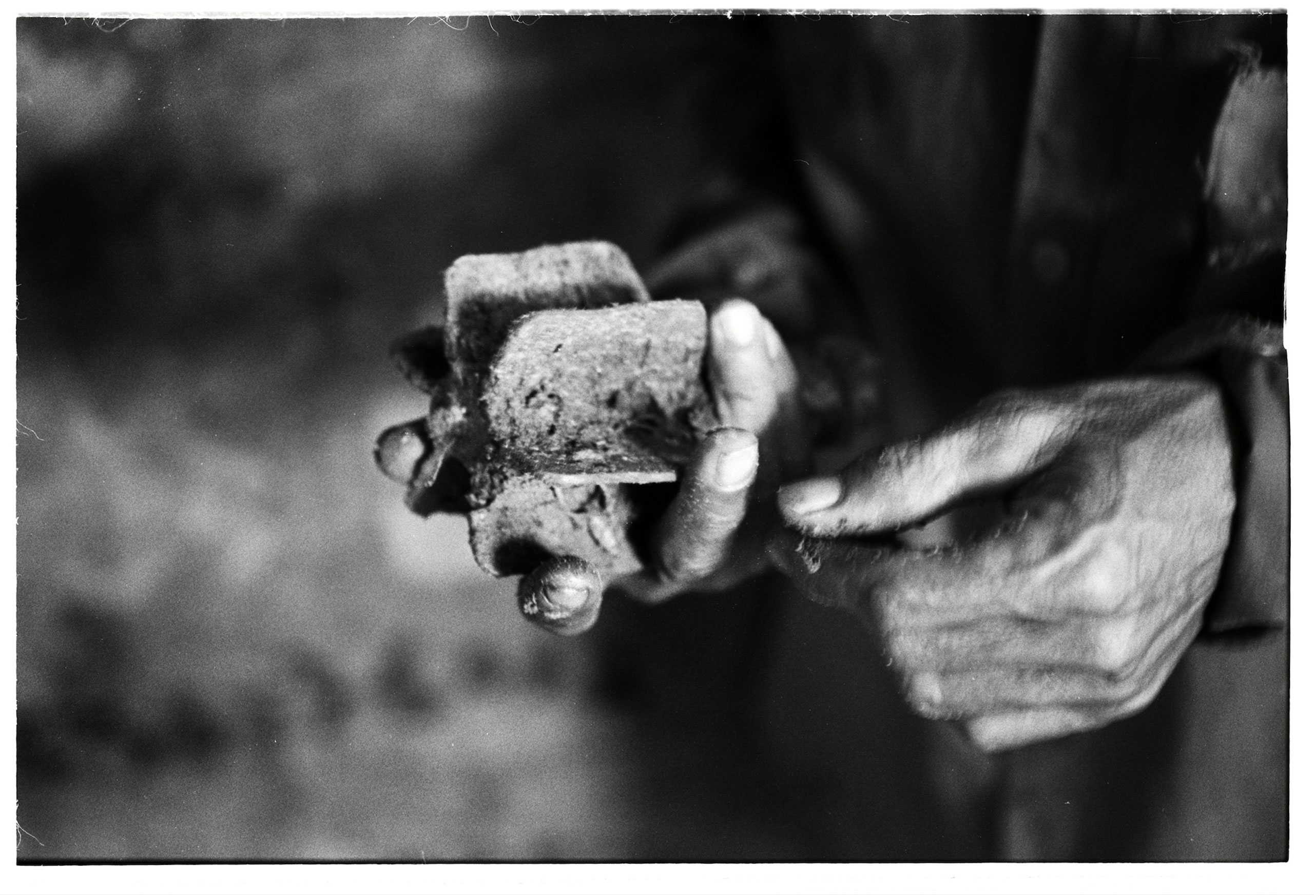 Vietnam 2014 A scrap metal collector assess a mortar shell she has just dug up. Each day she risks her life digging up UXO's which she sells to local scrap metal merchants for a few dollars.