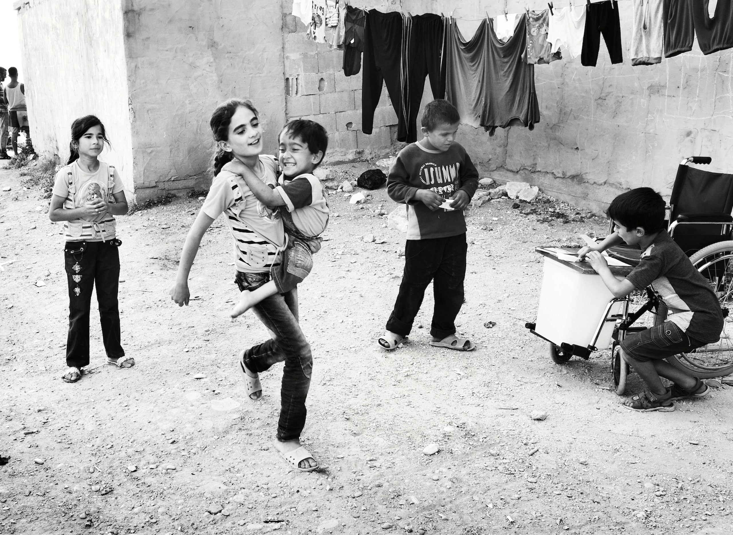Lebanon 2014 Iman has carried her sister Aya, who is paralysed from Spina Bifida since she was a baby. She carried Aya in this way when they fled Syria, a journey that lasted two months. In the makeshift camp where they now live, they play hopscotch with the other children.