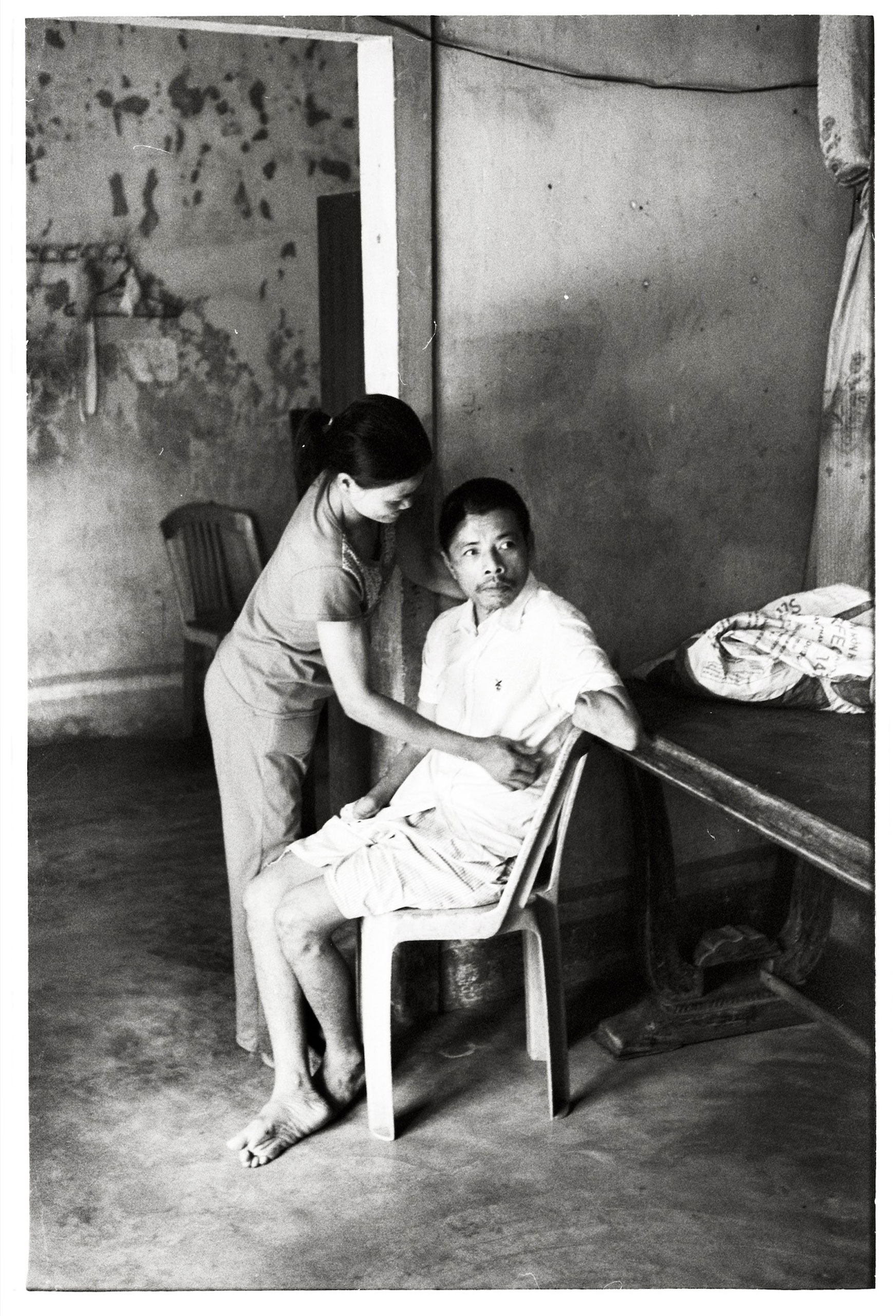 Vietnam 2014 Mr. Dinh Thu lost both arms and was left brain-damaged when an unexploded bomb detonated in his garden. His wife is now his full-time caretaker.