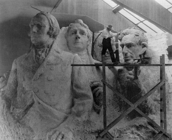 The sculptor of Mount Rushmore, Gutzon Borglum, with a model of the four presidents that included arms and hands.