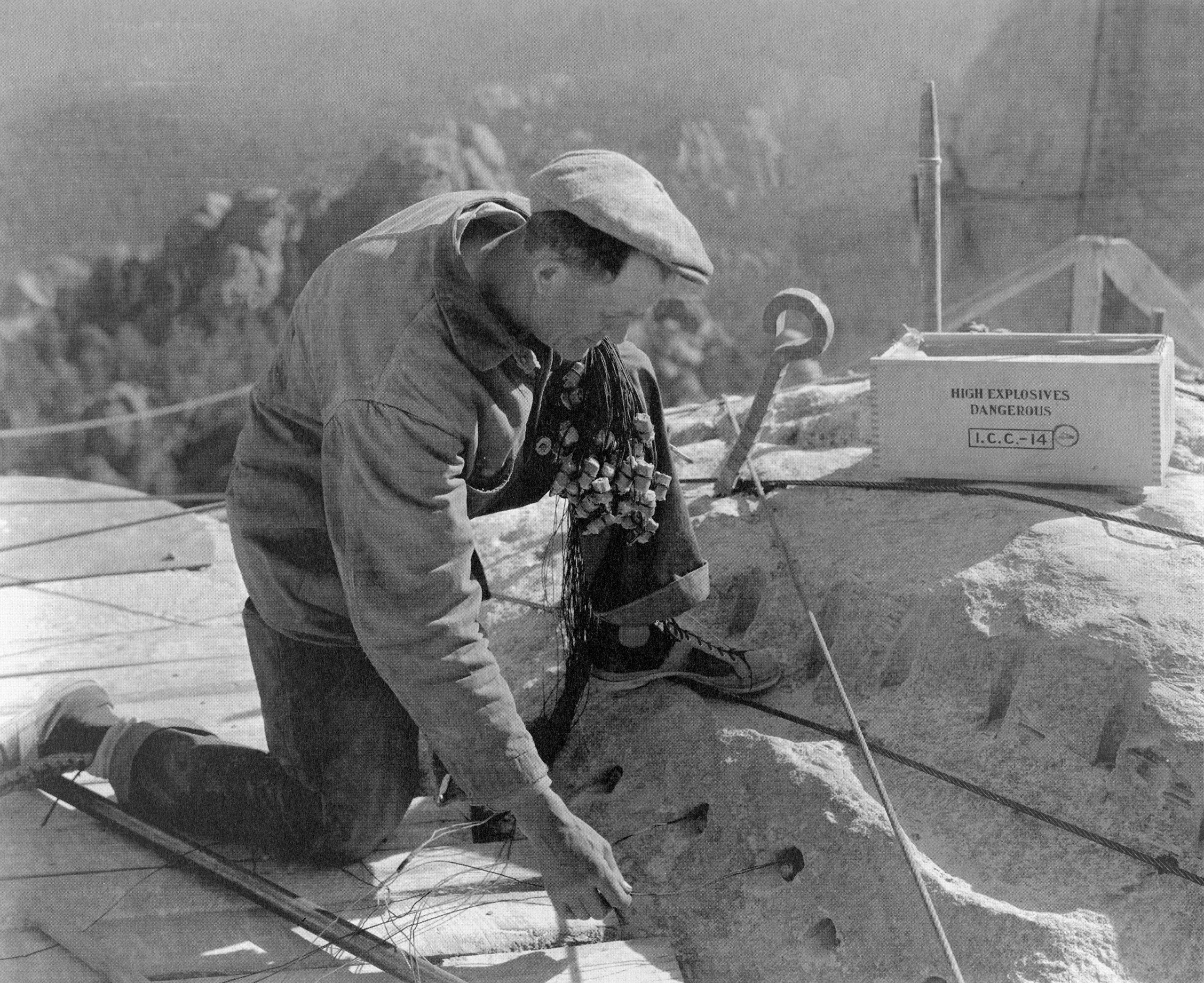 A powderman positions dynamite charges used to sculpt Mount Rushmore, c. 1930s.
