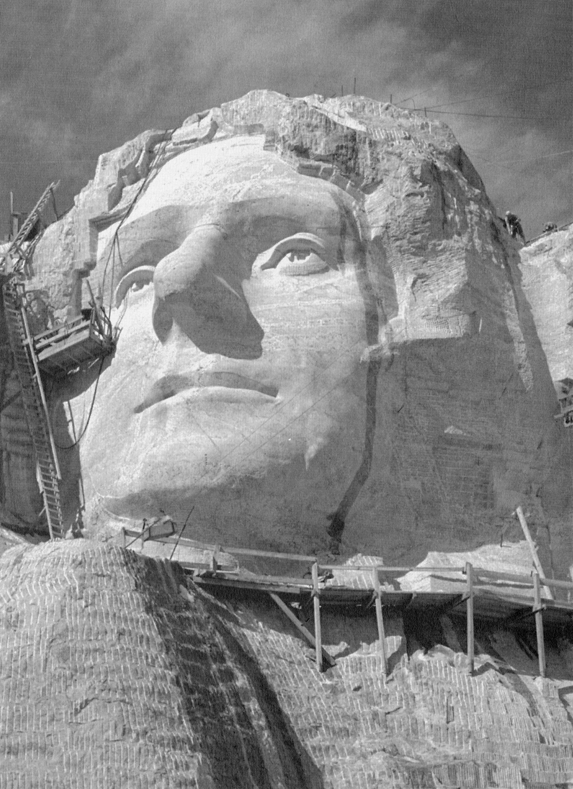 A close view of the face of Thomas Jefferson under construction, with drill marks below it, c. 1930s.