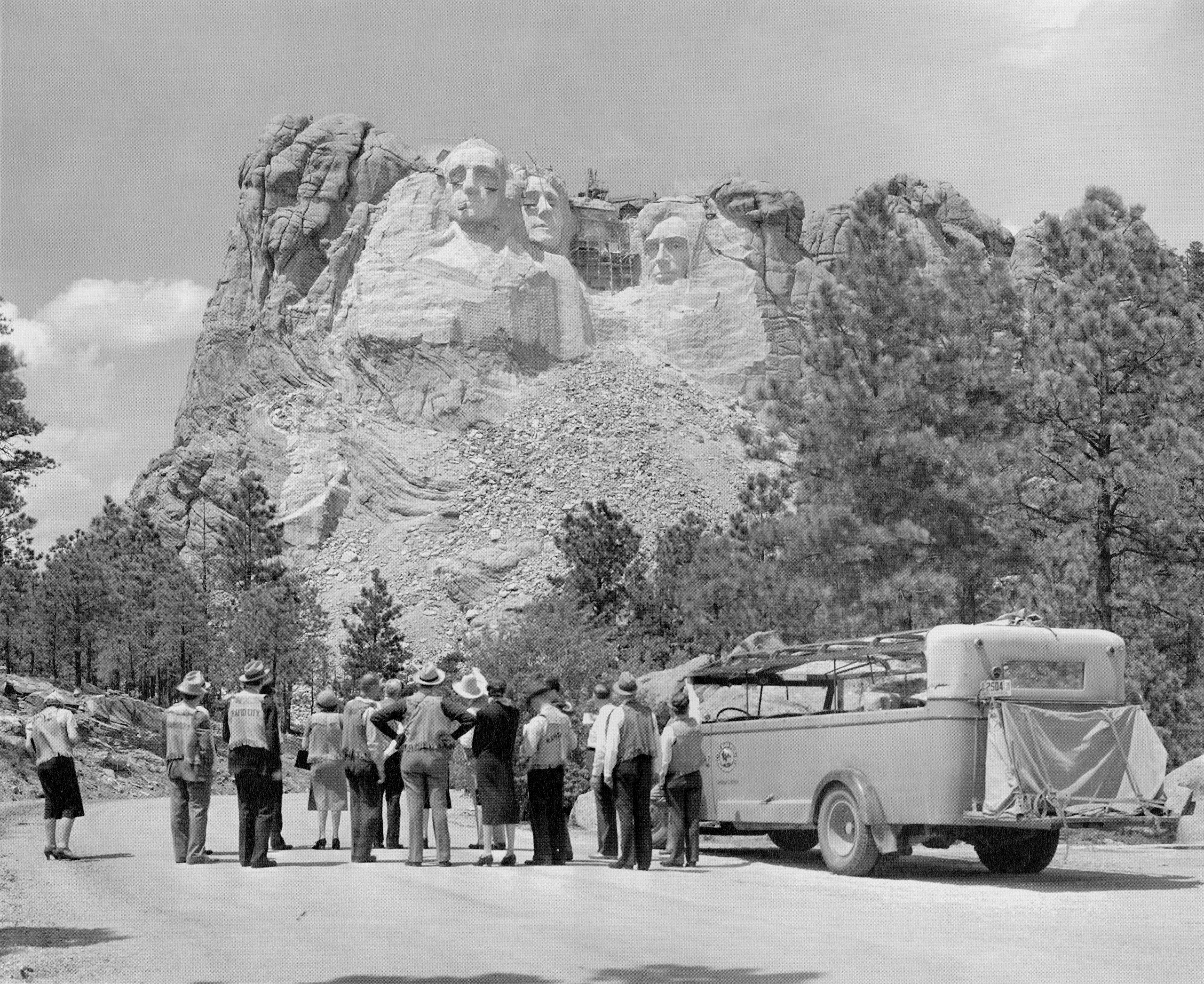 Tourists stopped to view Mount Rushmore while it was still under construction, c. 1930s.