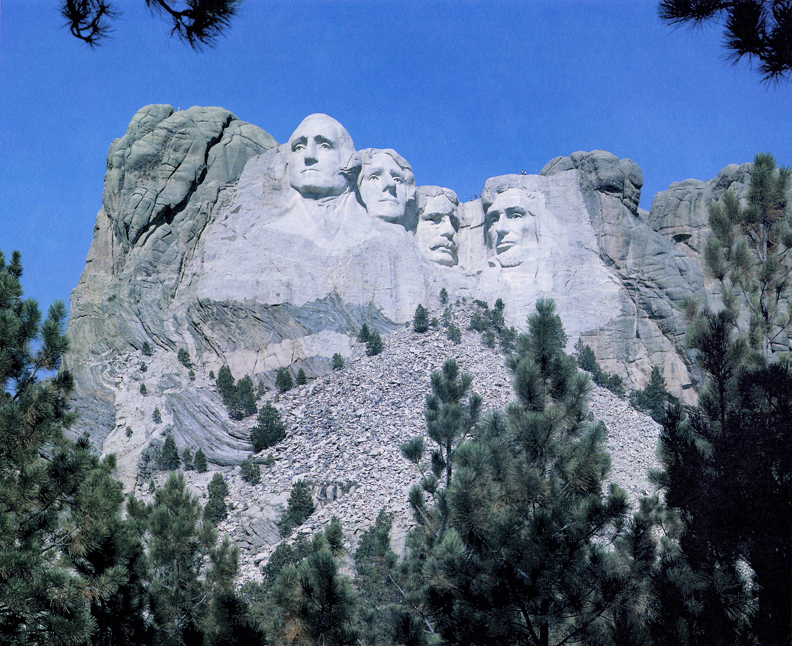 Mount Rushmore, as it appears today, with visitors climbing atop the monument.