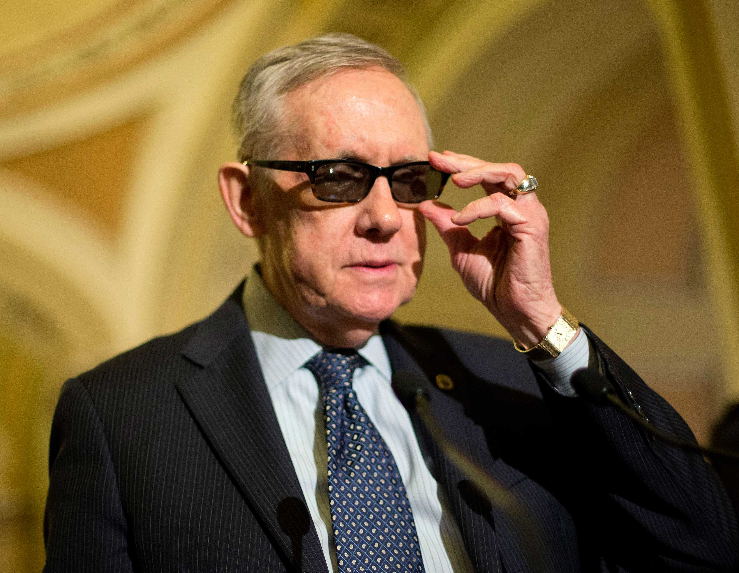 Senate Minority Leader Harry Reid of Nev. adjusts his glasses as he speaks to reporters on Capitol Hill in Washington, March 24, 2015.