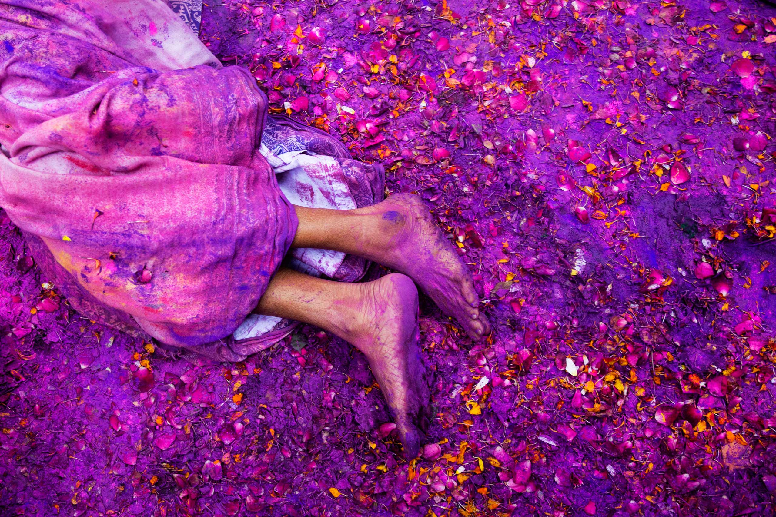 A Hindu widow lies on a sludgy ground filled with a mixture of colored powder, water and flower petals during celebrations to mark Holi, the Hindu festival of colors, at the Meera Sahabhagini Widow Ashram in Vrindavan, India, March 3, 2015.