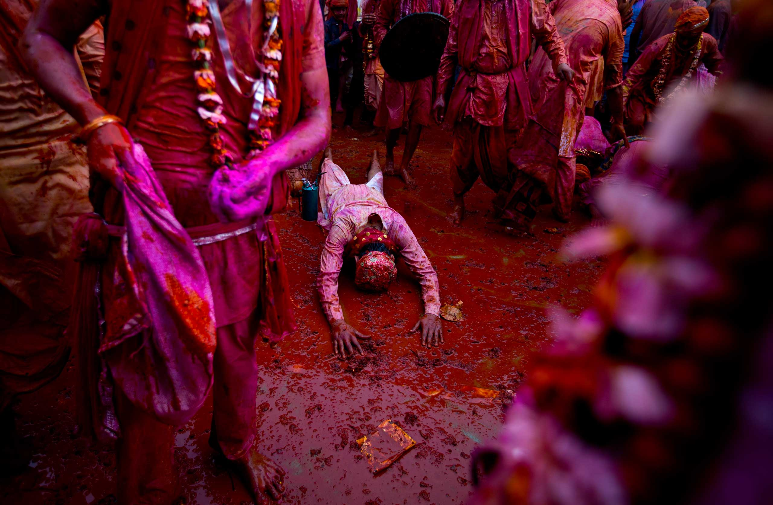An Indian Hindu devotee from Barsana village prostrates amid colors as he prays at the Nandagram temple, famous for Lord Krishna and his brother Balram, during Lathmar holi festival, in Nandgaon, India, Feb. 28, 2015.