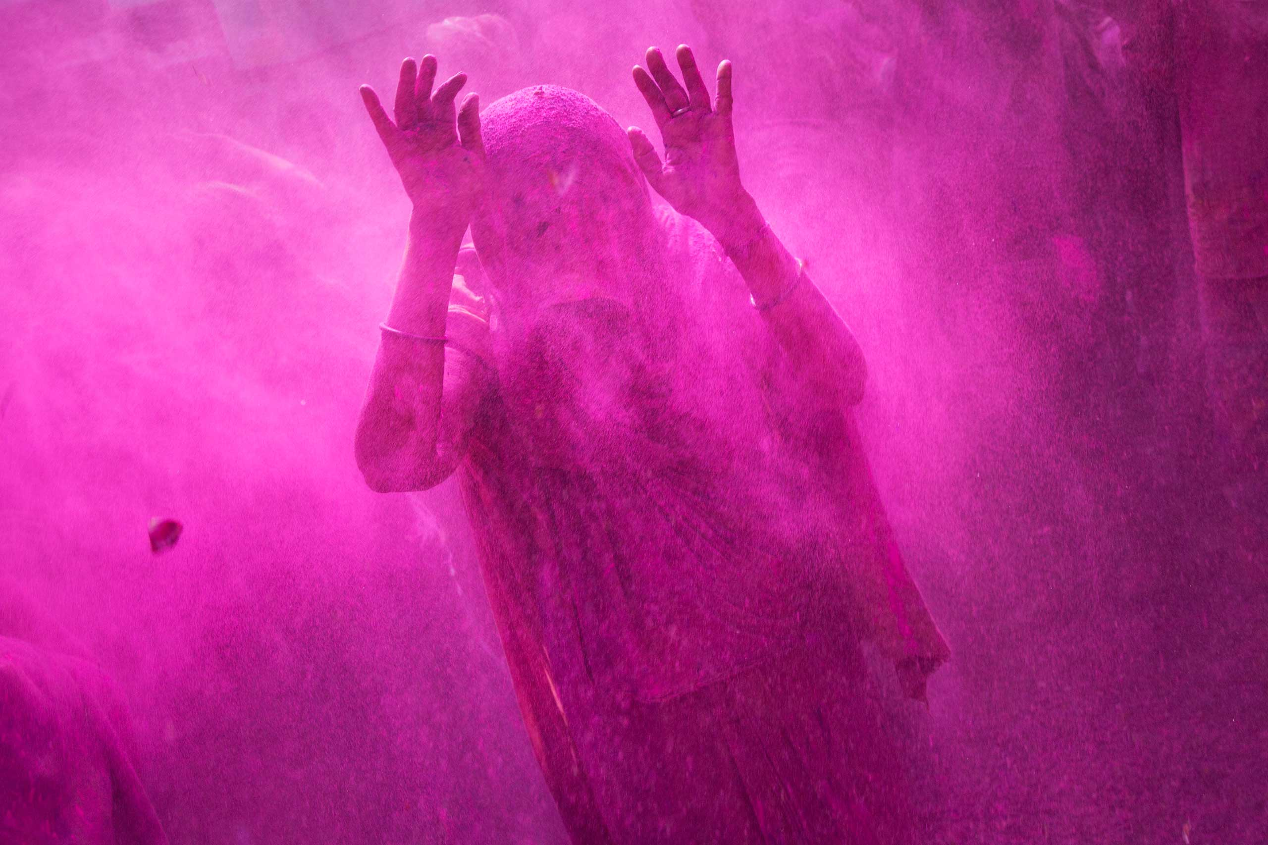 A widow raises her hands as others throw colored powder on her during celebrations marking Holi at the Meera Sahabhagini Widow Ashram in Vrindavan, India, March 3, 2015.