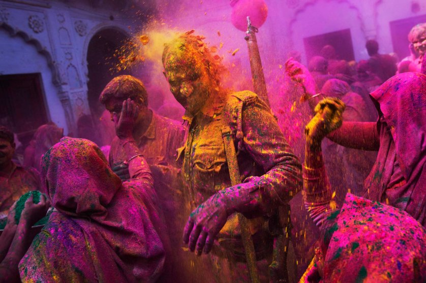Hindu widows throw colored powder on an Indian policeman as they celebrate Holi, the Hindu festival of colors, at the Meera Sahabhagini Widow Ashram in Vrindavan, India, March 3, 2015.
