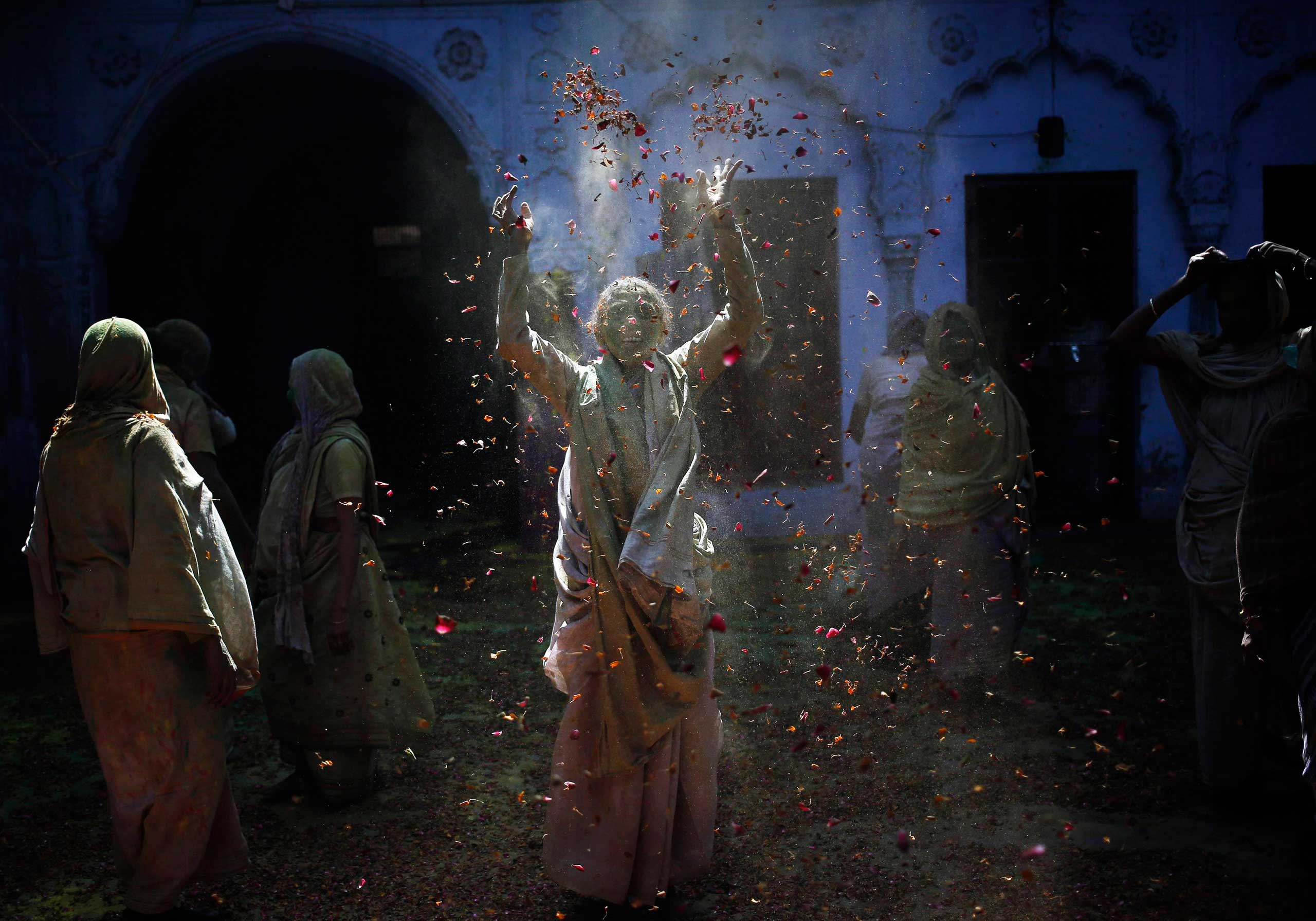 A widow throws flower petals as she, along with others, take part in the Holi celebrations organised by a non-governmental organisation Sulabh International at a widows' ashram at Vrindavan in the northern Indian state of Uttar Pradesh, March 4, 2015.
