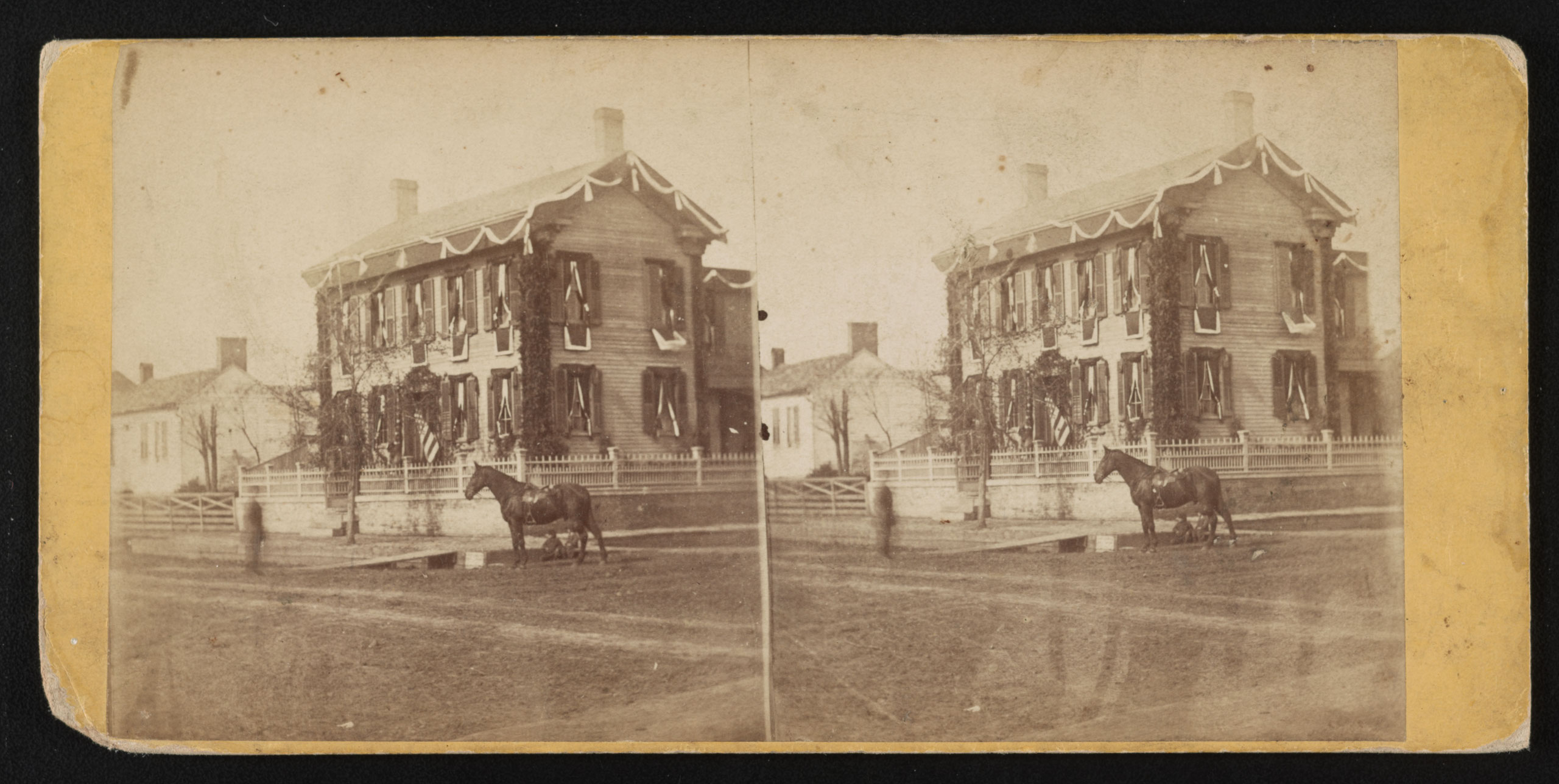 A street view of Abraham Lincoln's home in Springfield, Ill. draped in mourning on the day of his funeral. A horse stands near a wooden plank from the street to the sidewalk, circa 1865.