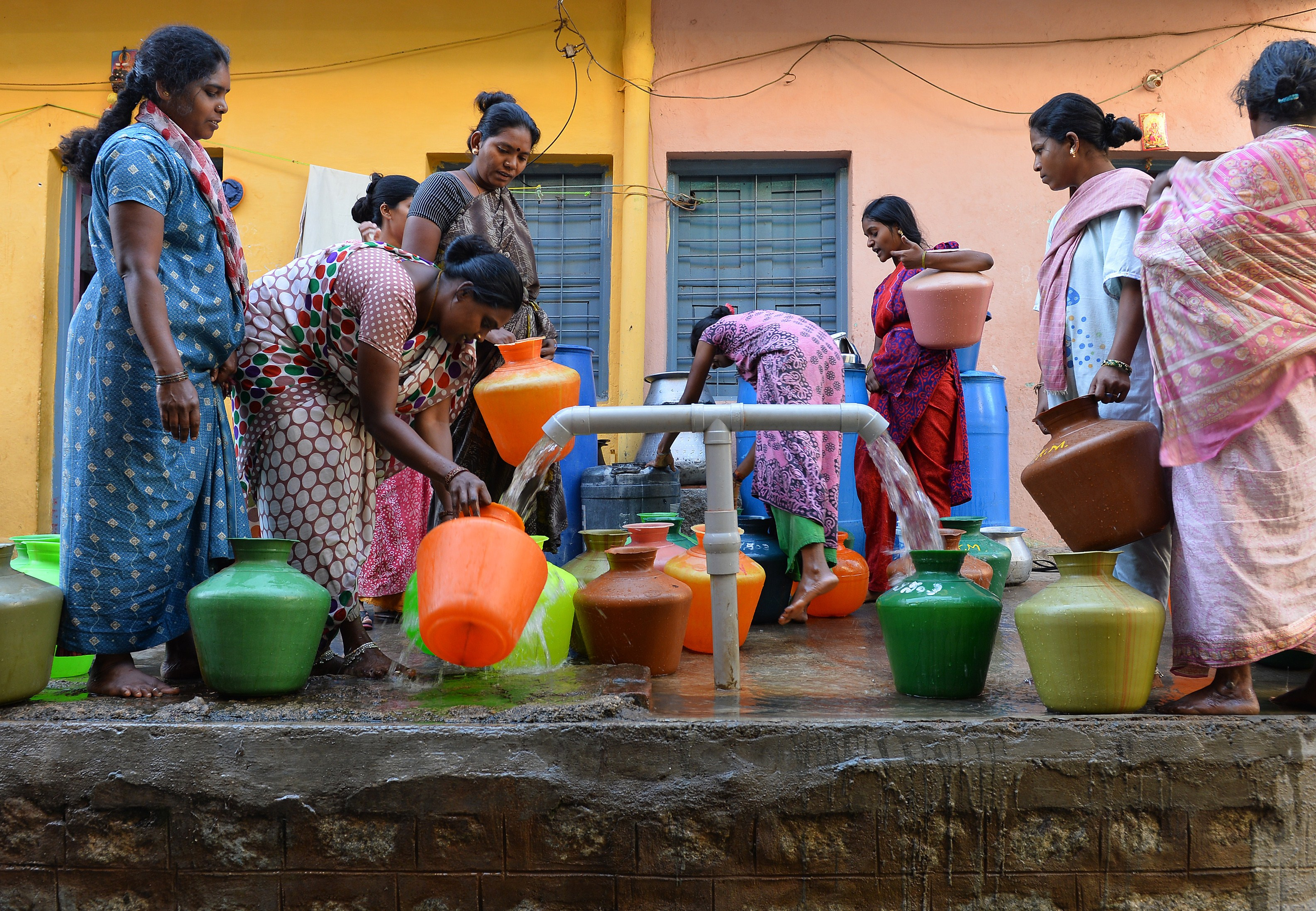 Residents in Bangalore wait to collect drinking water in plastic pots for their households on March 18, 2015.