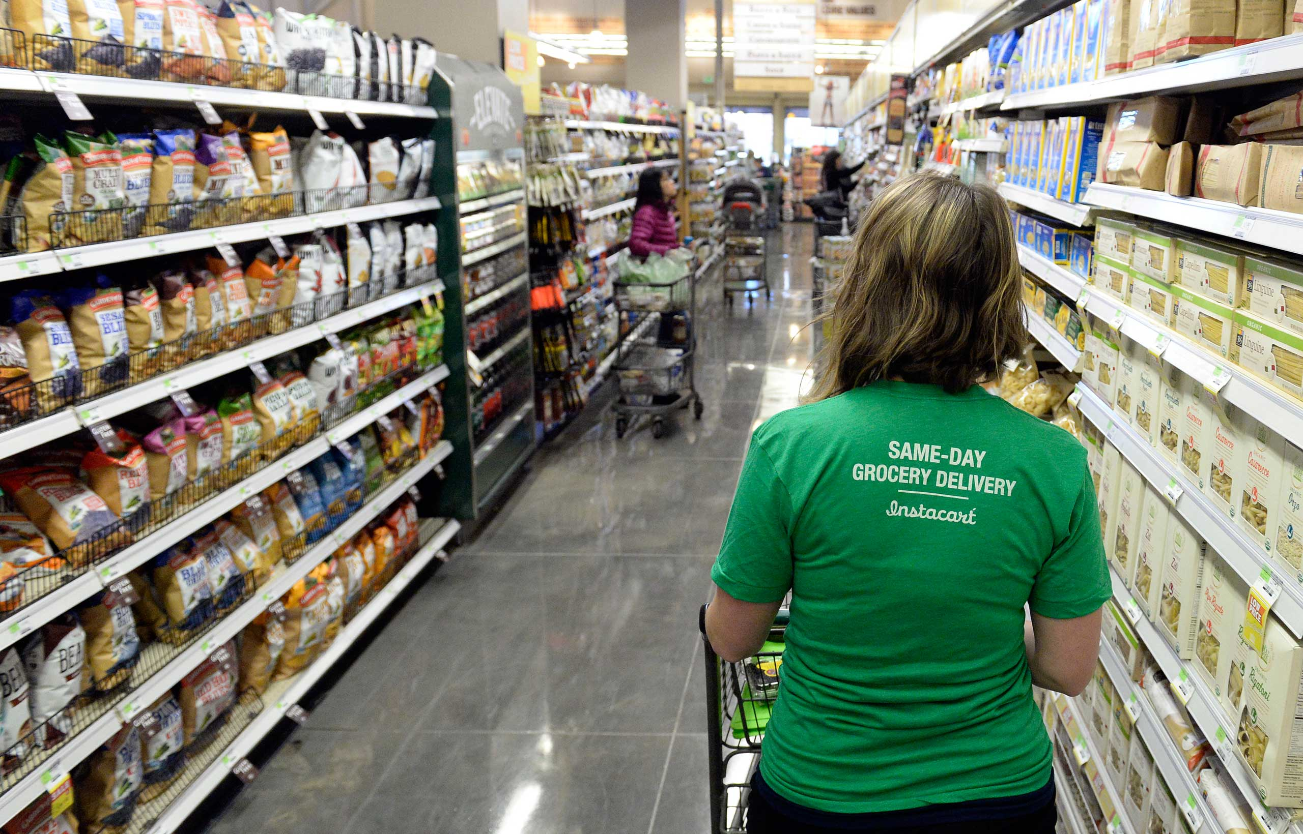 Instacart shopper Kaitlin Myers navigates through the aisles  at Whole Foods in Denver.