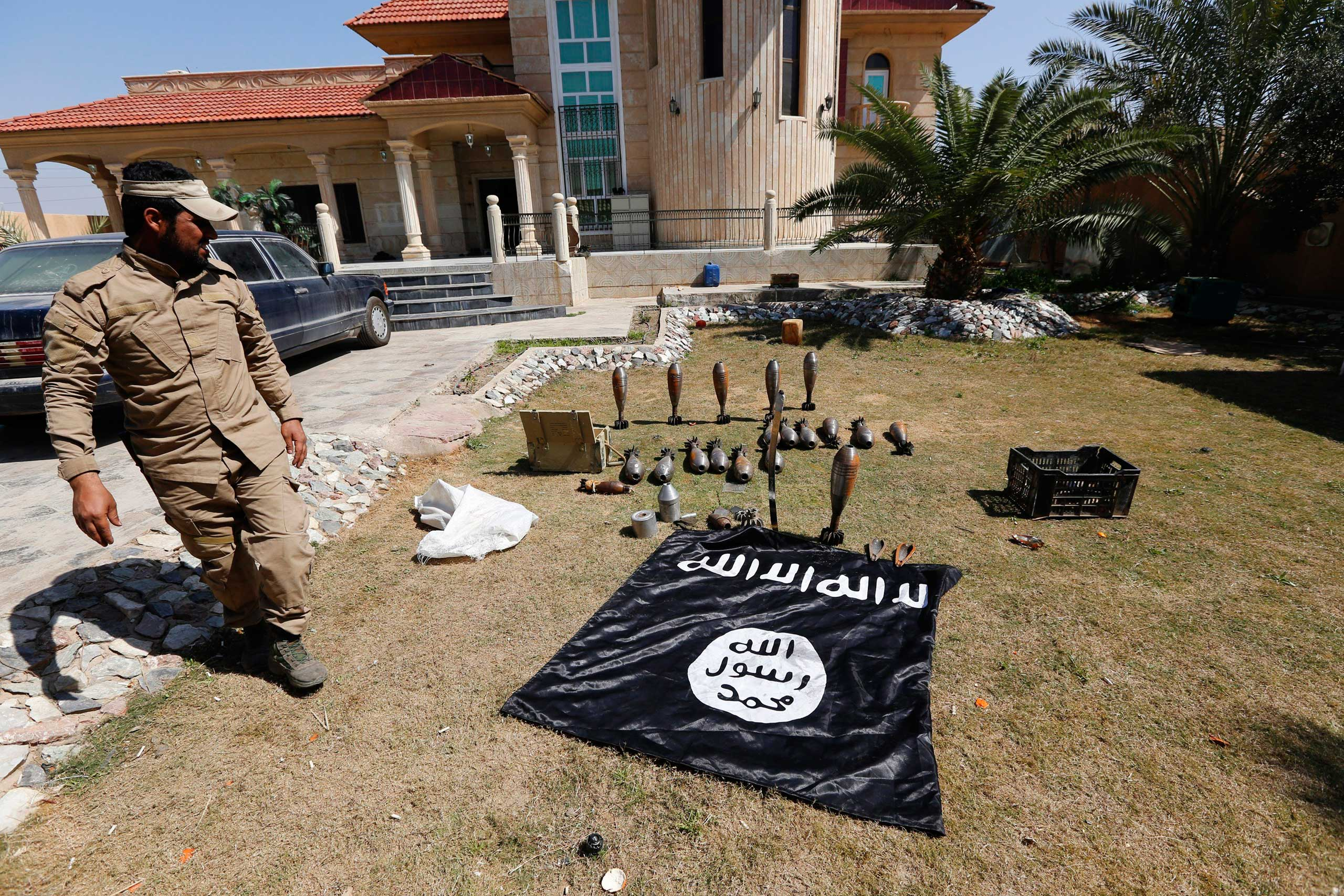 A Sunni fighter who has joined Shi'ite militia groups known collectively as Hashid Shaabi (Popular Mobilization), allied with Iraqi forces against ISIS, looks at an Islamic State flag and ammunition displayed in al-Alam Salahuddin province, March 15, 2015.