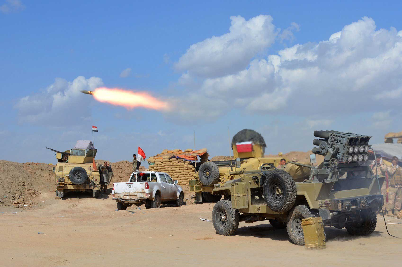 Iraqi government forces and allied militias fire weaponry from a position in the northern part of Diyala province, bordering Salaheddin province, as they take part in an assault to retake the city of Tikrit from ISIS militants, March 2, 2015.