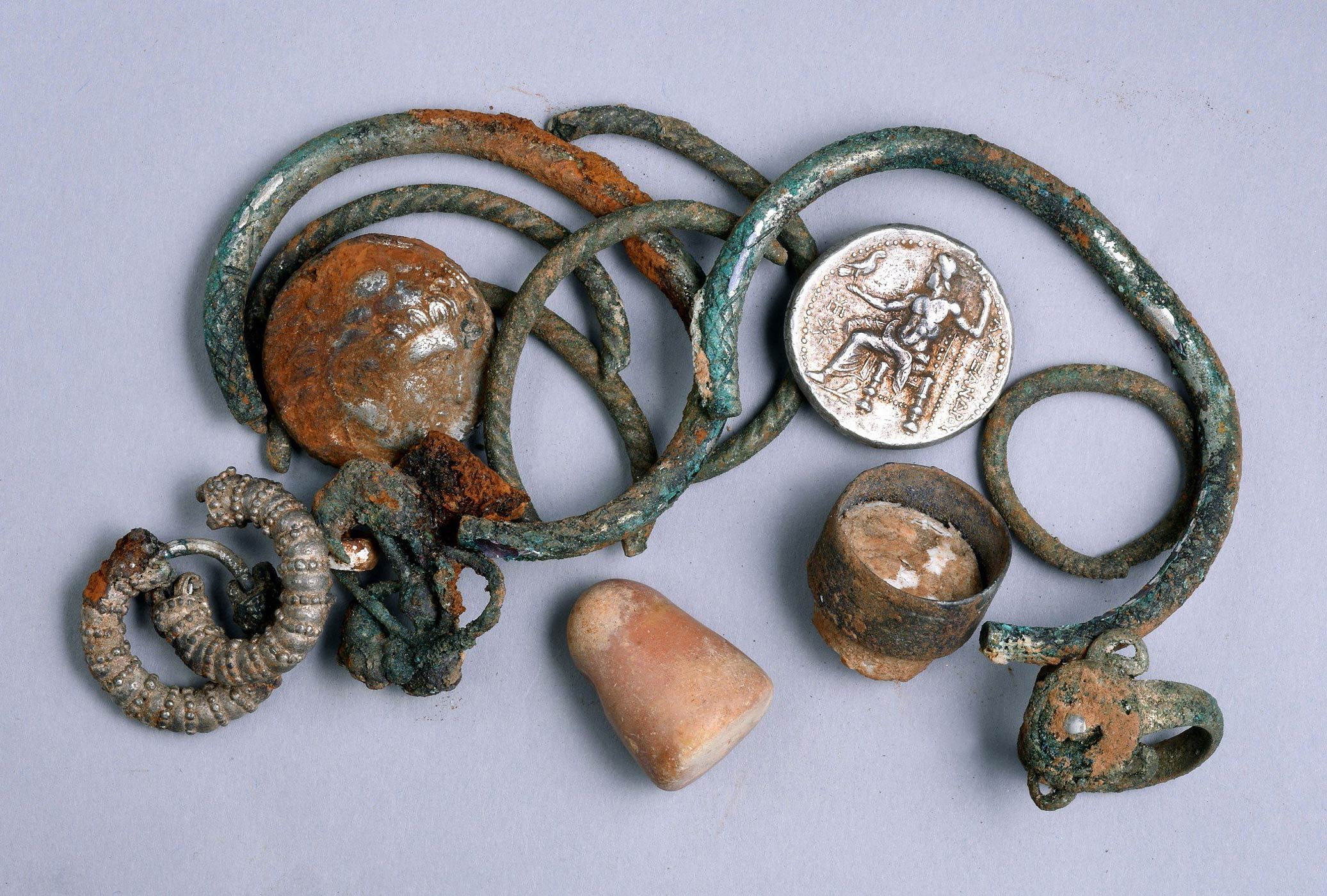 Ancient coins and other objects that were found by chance in a cave in northern Israel.