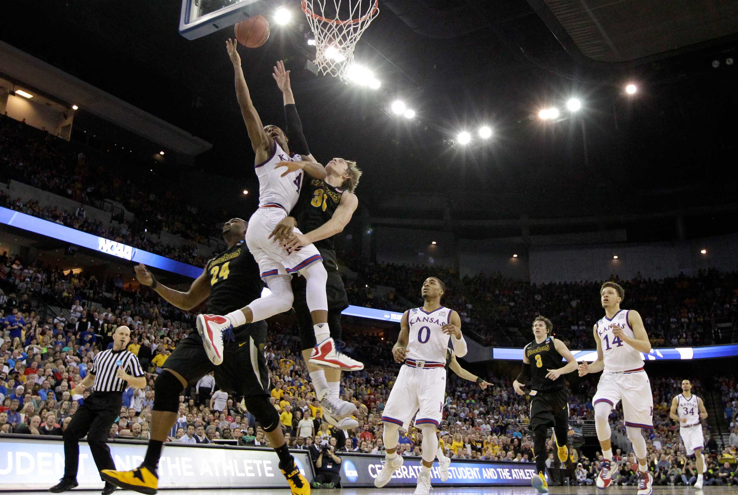 Kansas guard Devonte Graham (4) drives to the basket between Wichita State defenders Shaquille Morris (24) and Ron Baker (31) during the second half of an NCAA college basketball tournament Round of 32 game on March 22, 2015, in Omaha, Neb.