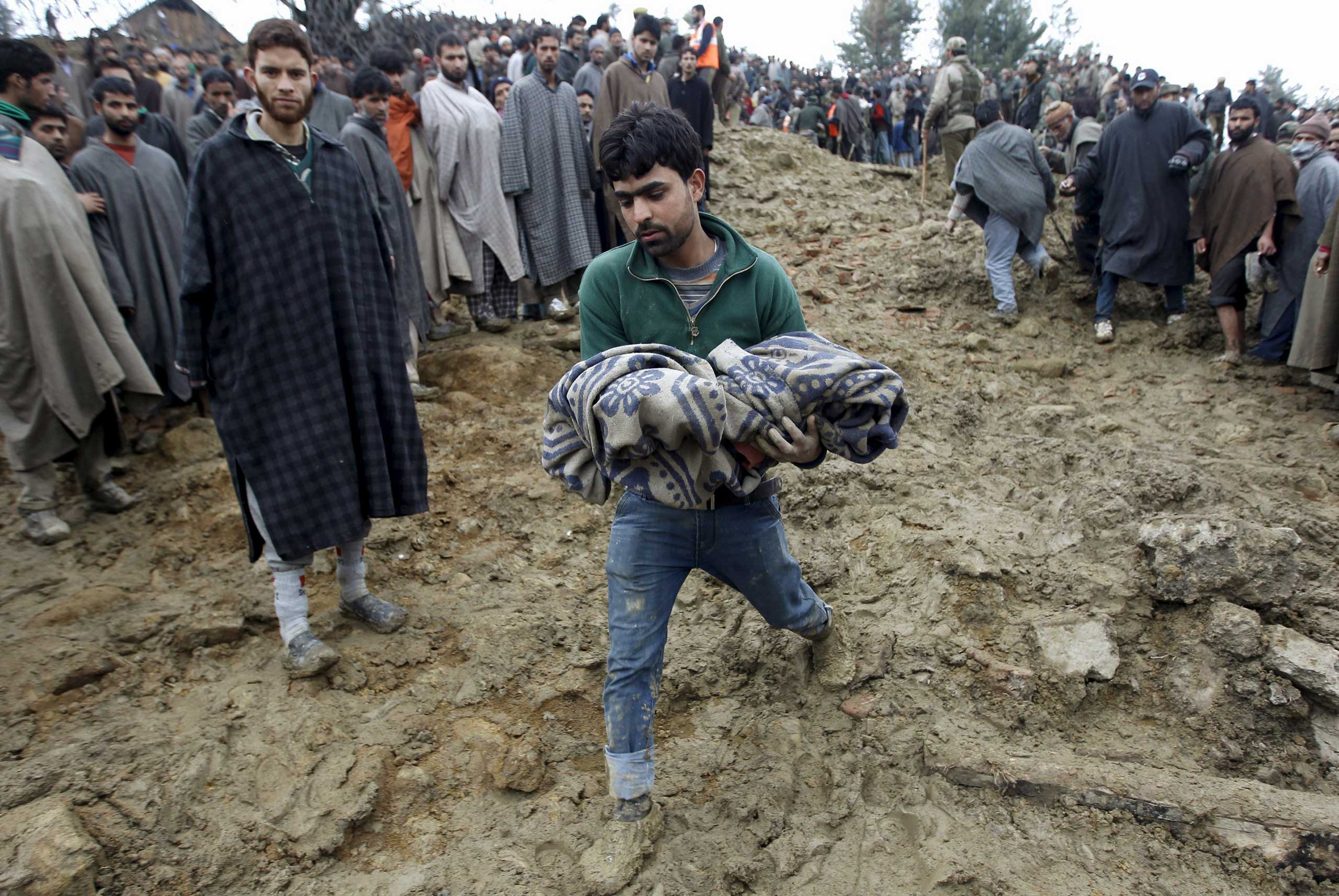 A Kashmiri man in the village of Laden carries the body of a child after it was pulled out from the rubble after a hillside collapsed onto a house on March 30, 2015.