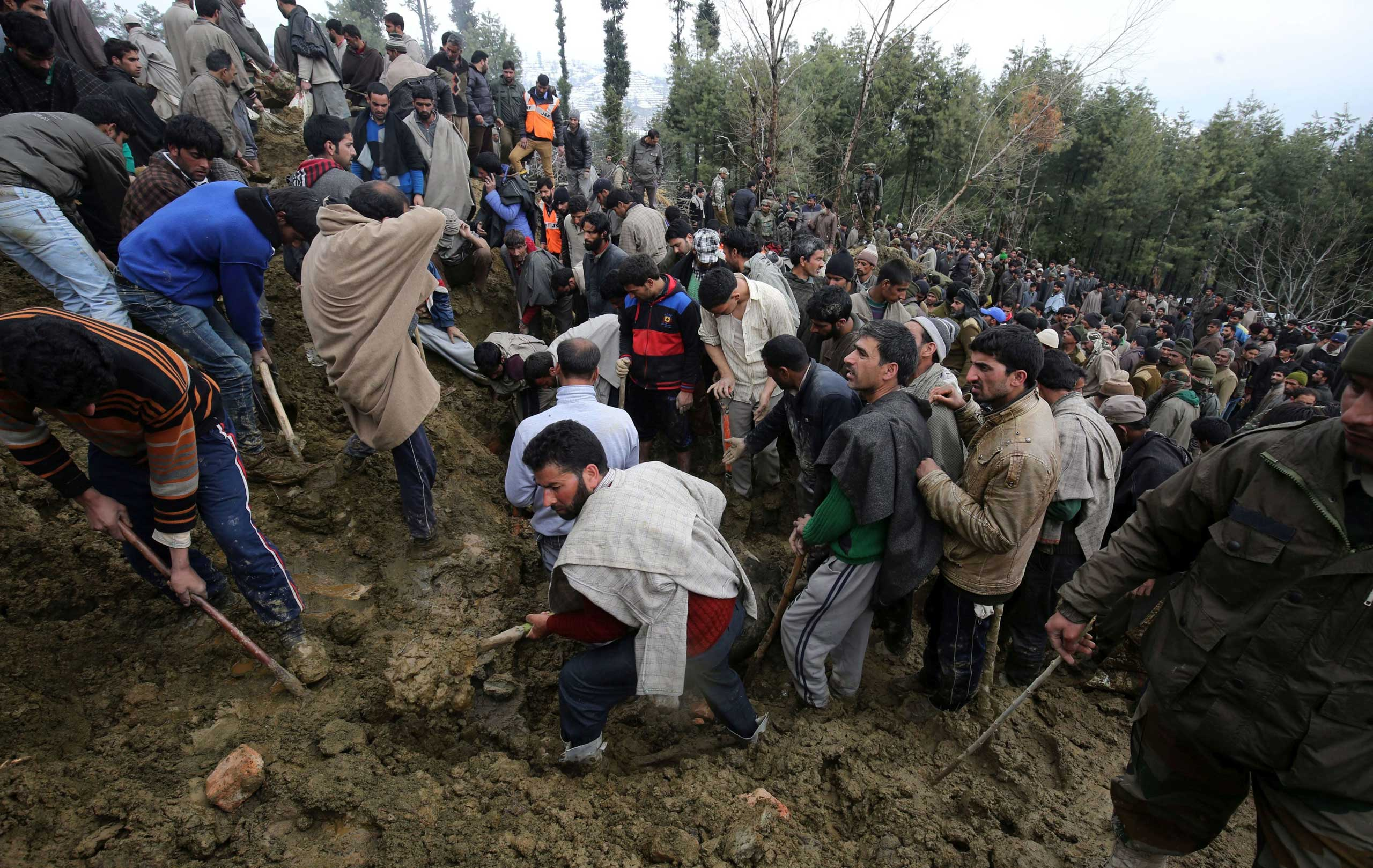 Kashmiri villagers look for missing residents following a landslide due to heavy rainfall in the village of Laden on March 30, 2015.