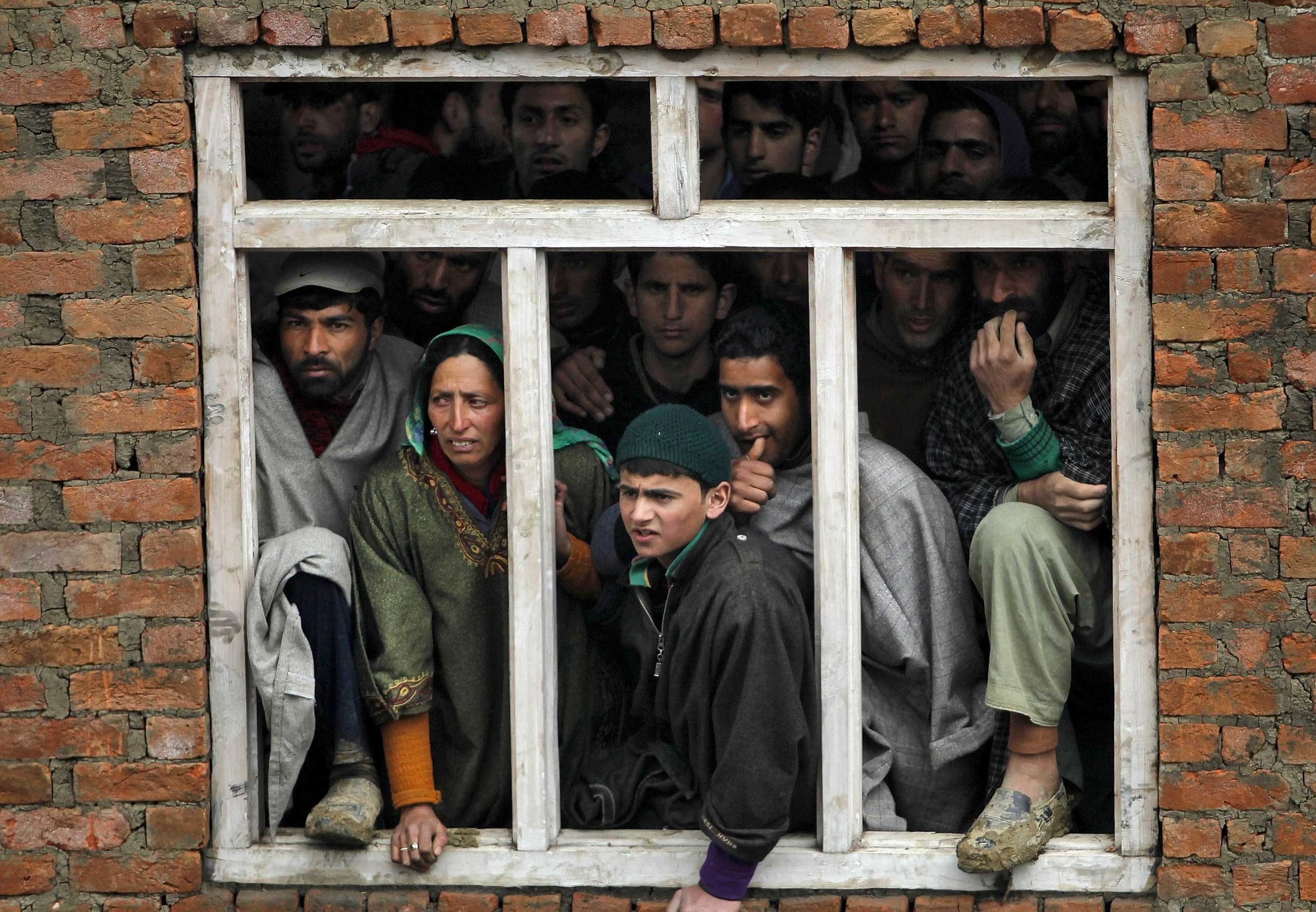 Kashmiri villagers watch the rescue operation at the site of a damaged home after a hillside collapsed onto it in the village of Laden on March 30, 2015.