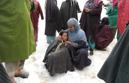 Kashmiri villagers gather during rescue efforts following a landslide due to heavy rainfall in the village of Laden near Chadoora, west of Srinagar, on March 30, 2015.