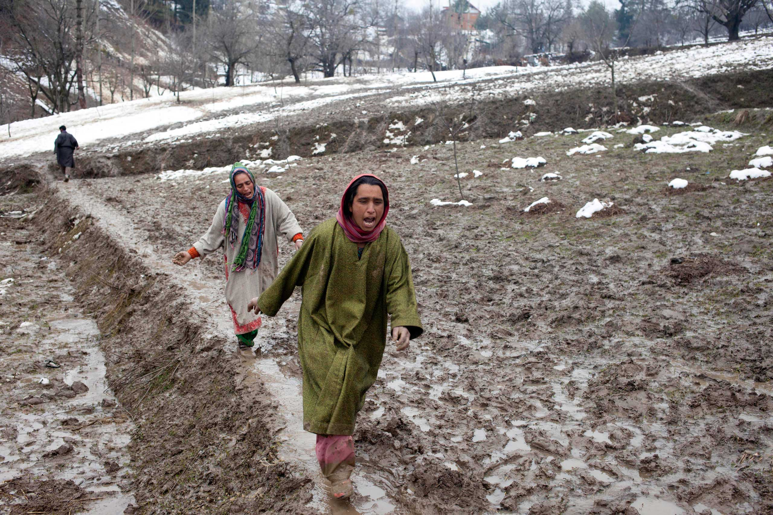 Kashmiri women wail and rush towards  the body of a relative, victim of a landslide, in the village of Laden on March 30, 2015.