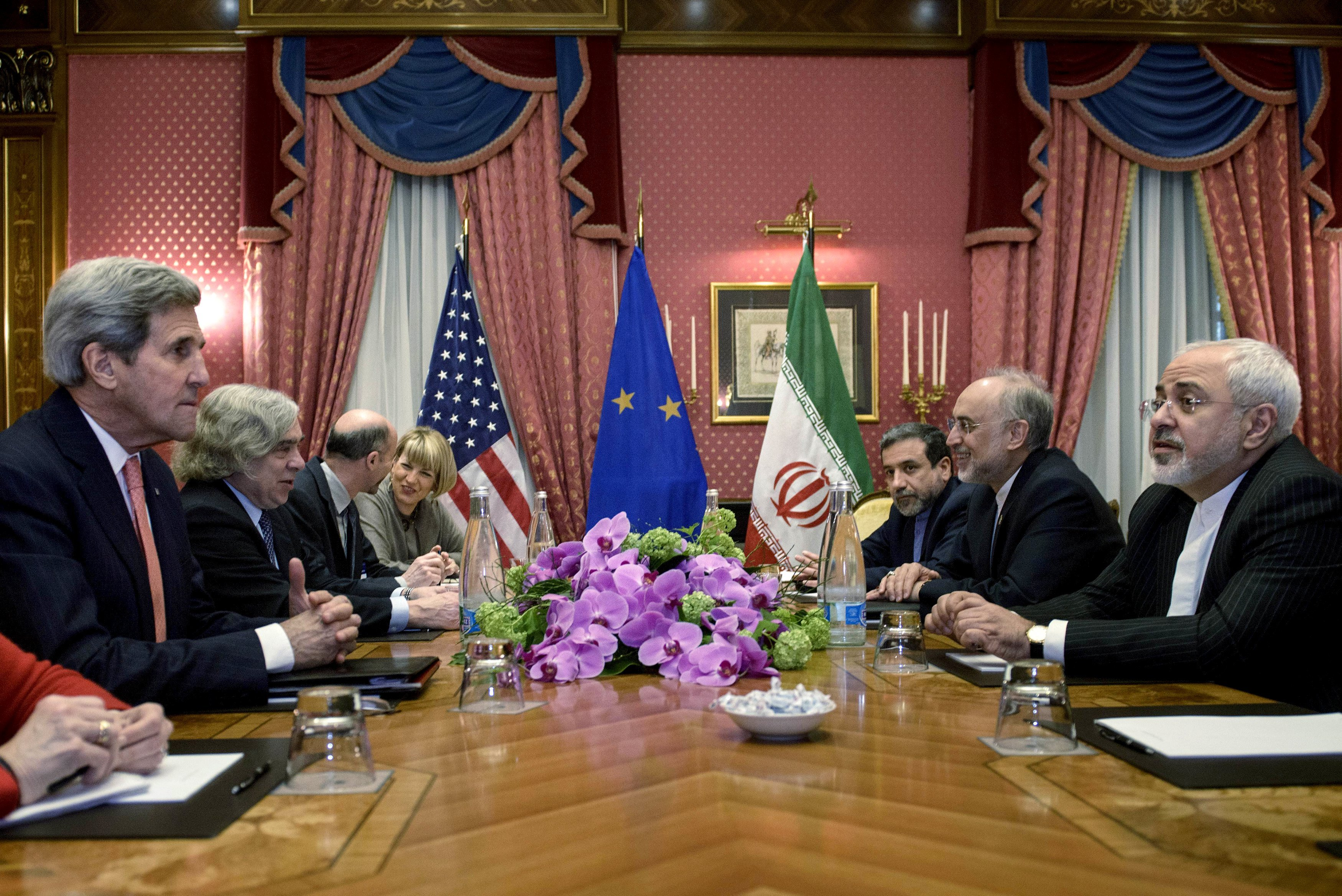 Secretary of State John Kerry, Iranian Foreign Minister Javad Zarif and others wait for a meeting at the Beau Rivage Palace Hotel on March 27, 2015 in Lausanne, Switzerland.