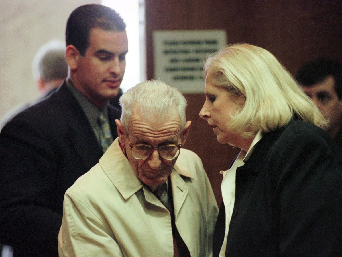 Dr. Jack Kevorkian talks with jury consultant Ruth Holmes (R) as Brad Feldman, one of his legal advisors, listens after Kevorkian's  arraignment in Oakland County Circuit Court, Dec. 16, 1998
