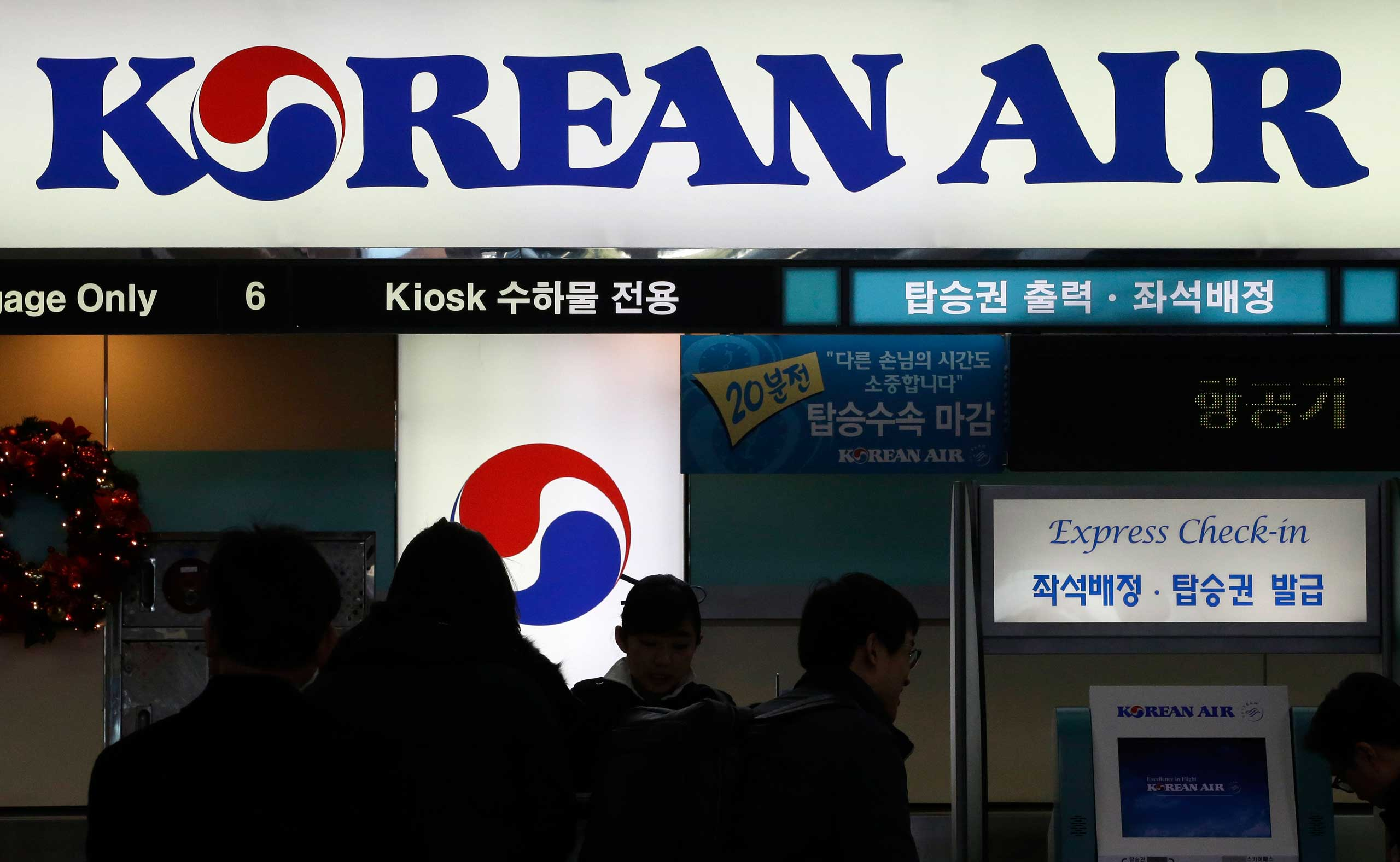 Passengers wait to check in at the domestic check-in desk of Korean Air Lines Co. at Gimpo Airport in Seoul, South Korea, Dec. 2014.