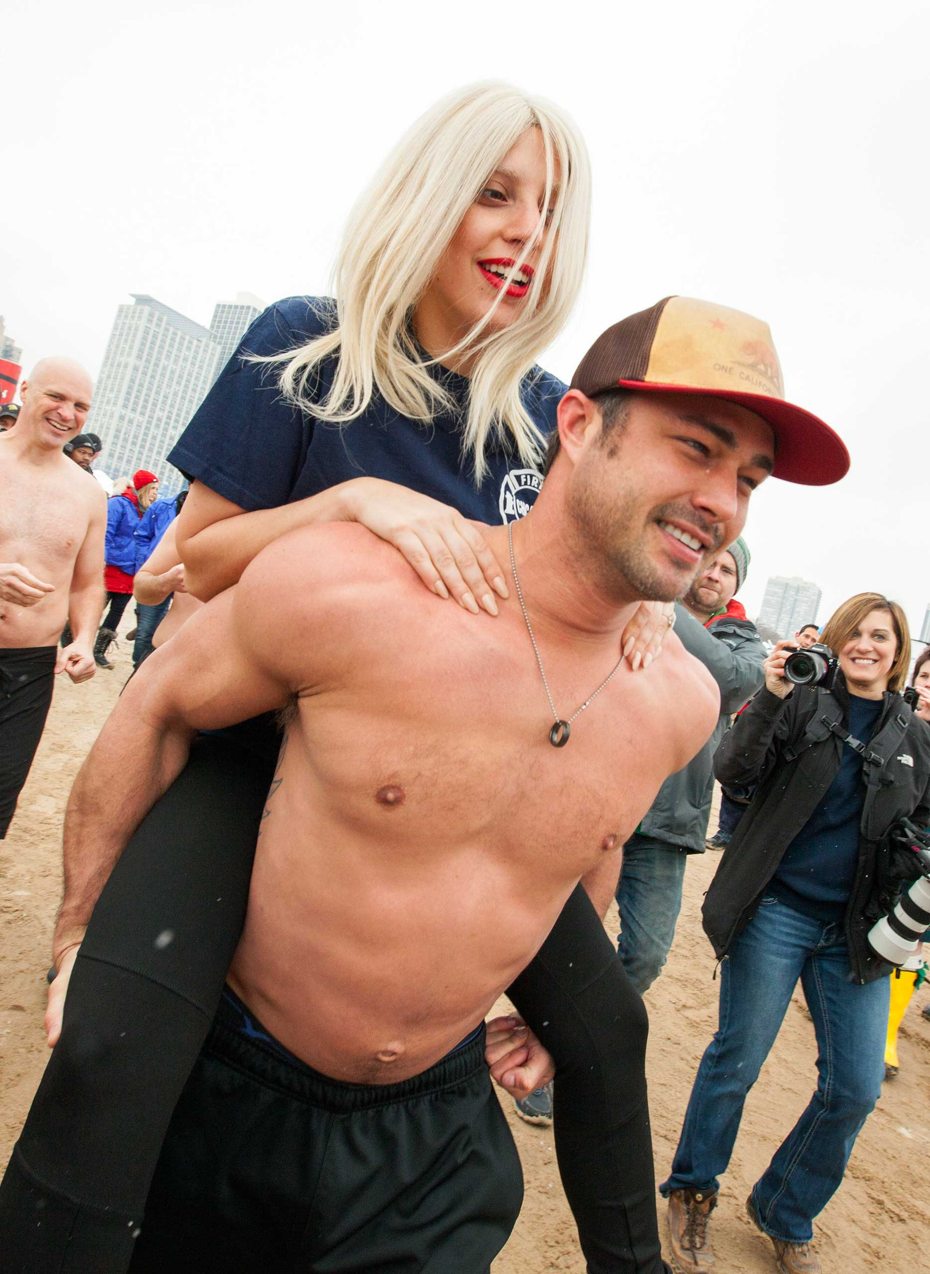 Lady Gaga, top, gets a piggy back ride from her fiancée, Taylor Kinney, as they and members of the  Chicago Fire  cast take part in the Chicago Polar Plunge at North Avenue Beach on March 1, 2015 in Chicago.