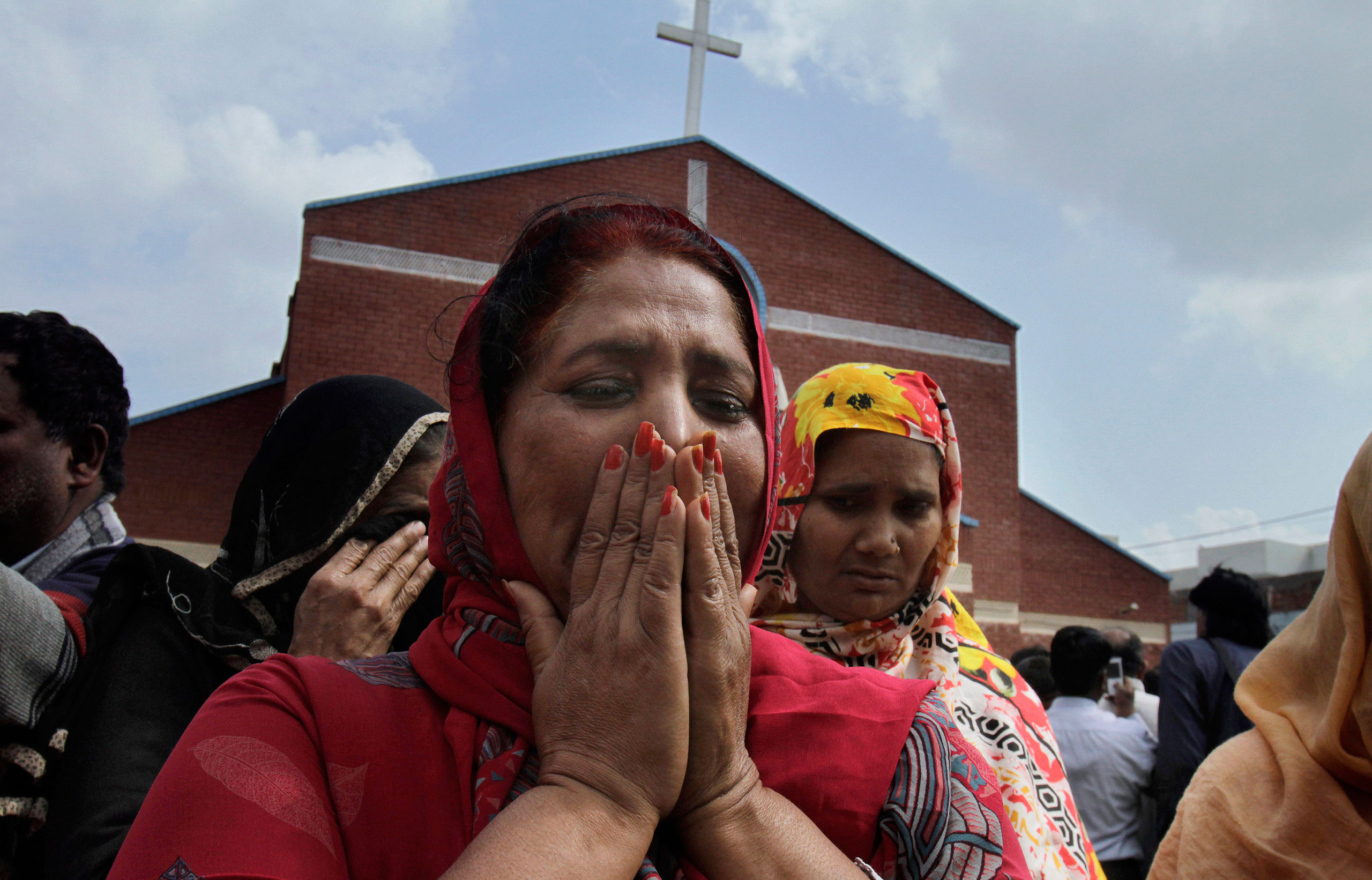 Pakistani Christian women mourn as they gather at a church damaged from a suicide bombing attack in Lahore, Pakistan, March 15, 2015.