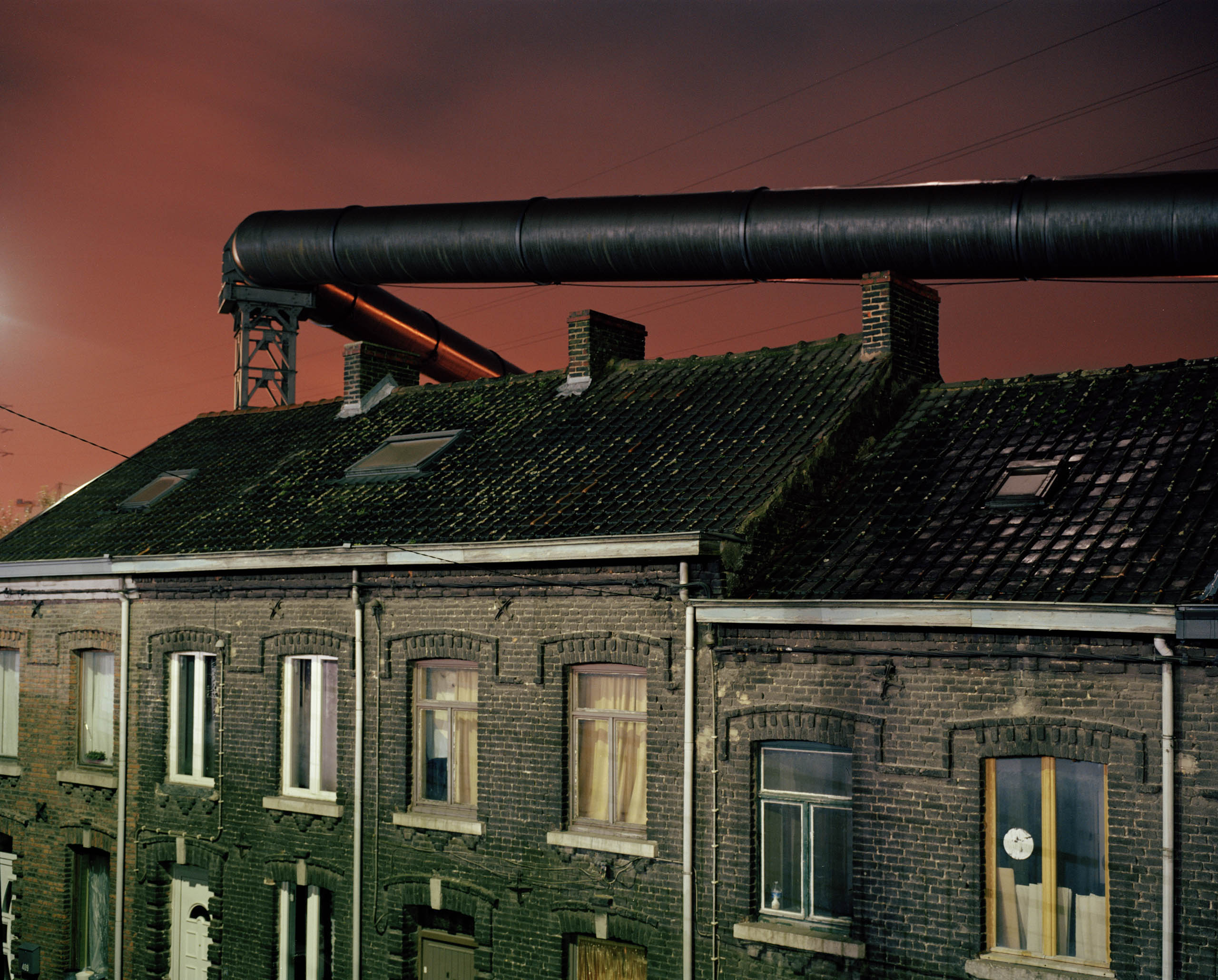 The gas supply tubes run along the houses built near the steel factories of Charleroi. Before the electric upgrade of the blast furnace these tubes used to provide the energy necessary to this operation. The factory and furnace infringe and loom over the lives of the inhabitants.