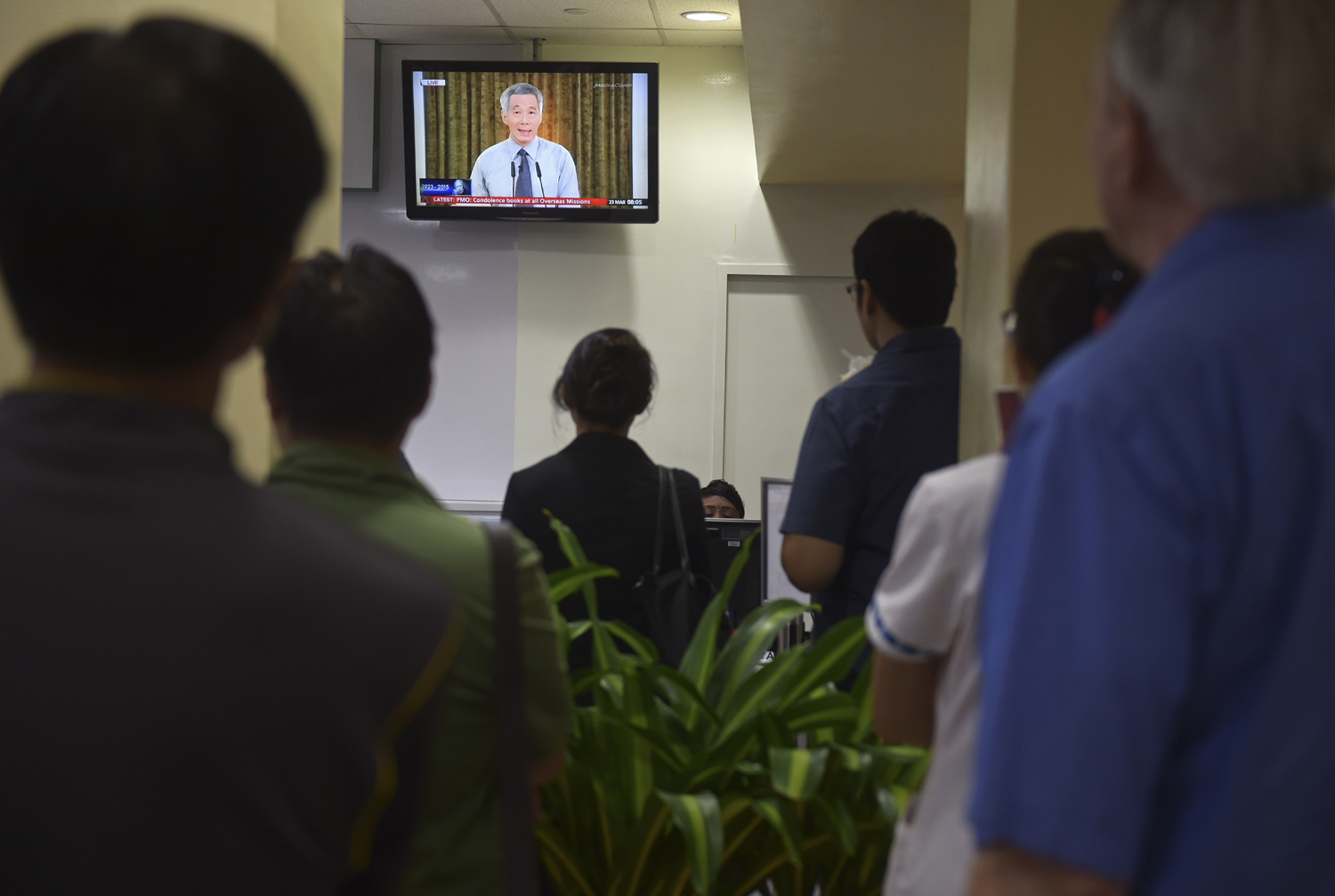 A live broadcast by Singaporean Prime Minister Lee Hsien Loong on the death of his father is watched in a reception area at a hospital where the city-state's first Prime Minister Lee Kuan Yew passed away on March 23, 2015, in Singapore