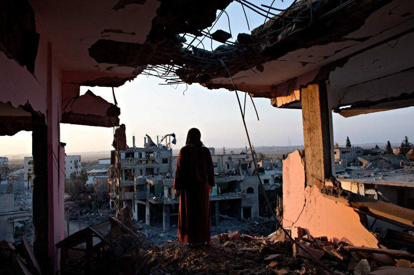 Hidya Atash stands on the top floor of her home as she overlooks the destruction in Shujayea in Gaza at dawn Aug. 8, 2014.