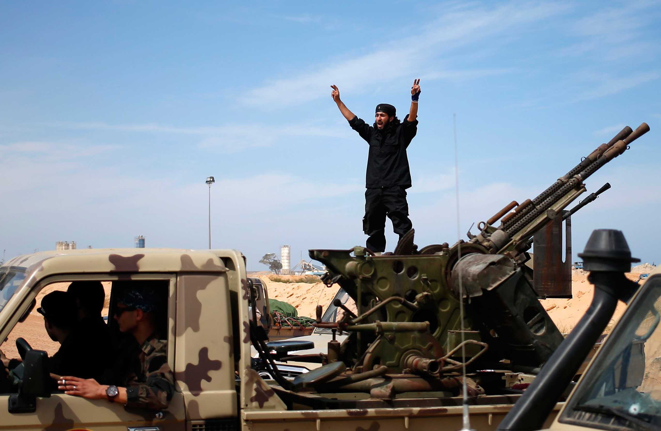 A fighter from Misrata shouts to his comrades as they move to fight ISIS militants near Sirte March 15, 2015.